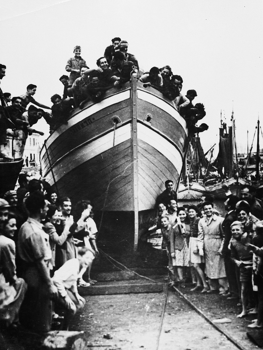 Jewish DPs gather in and around their newly constructed fishing boat during its christening ceremony at the Migdalor hachshara, a maritime Zionist collective in Fano, Italy.