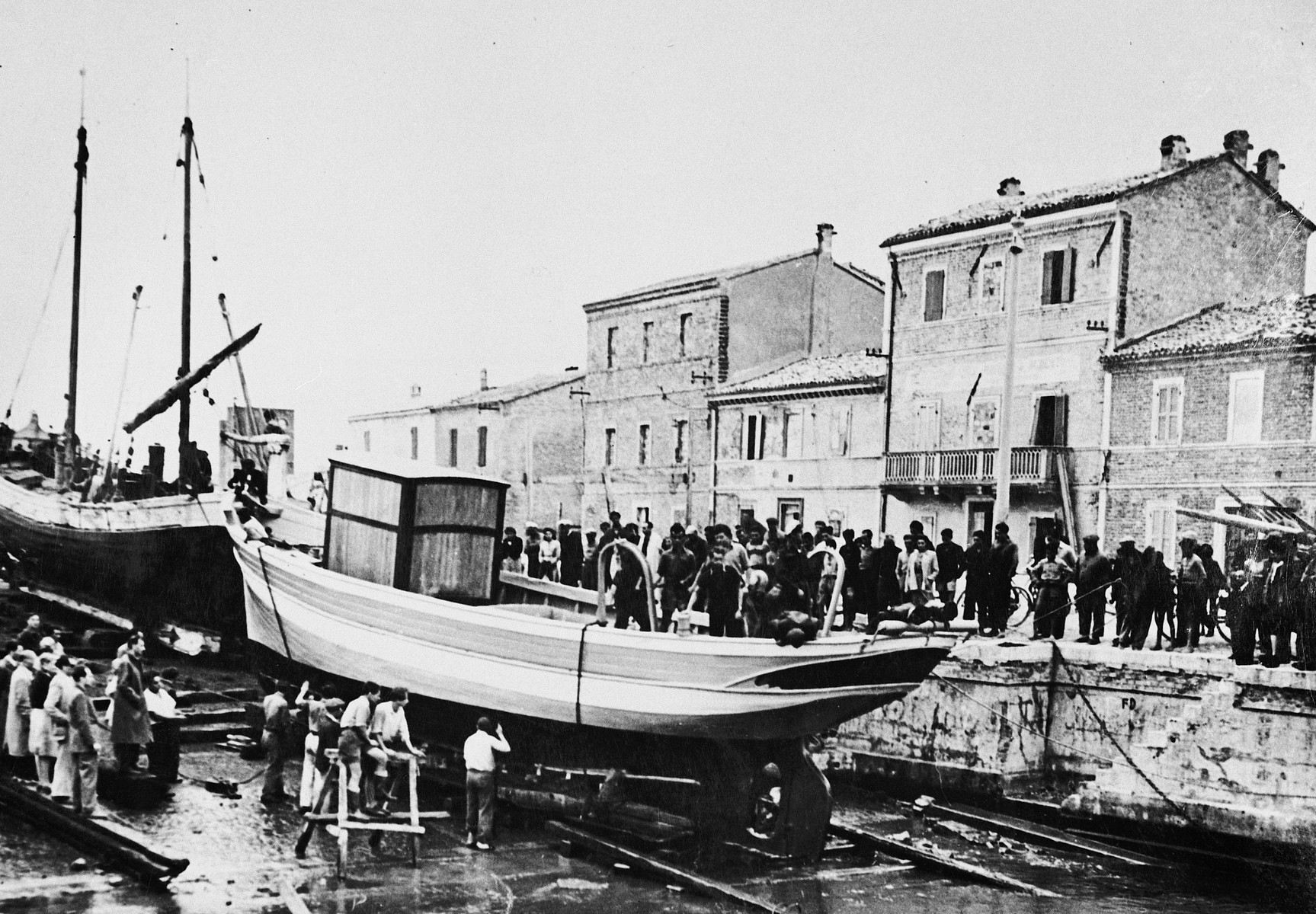 Jewish DPs gather on the pier alongside their newly constructed fishing boat during its christening ceremony at the Migdalor hachshara, a maritime Zionist collective in Fano, Italy.