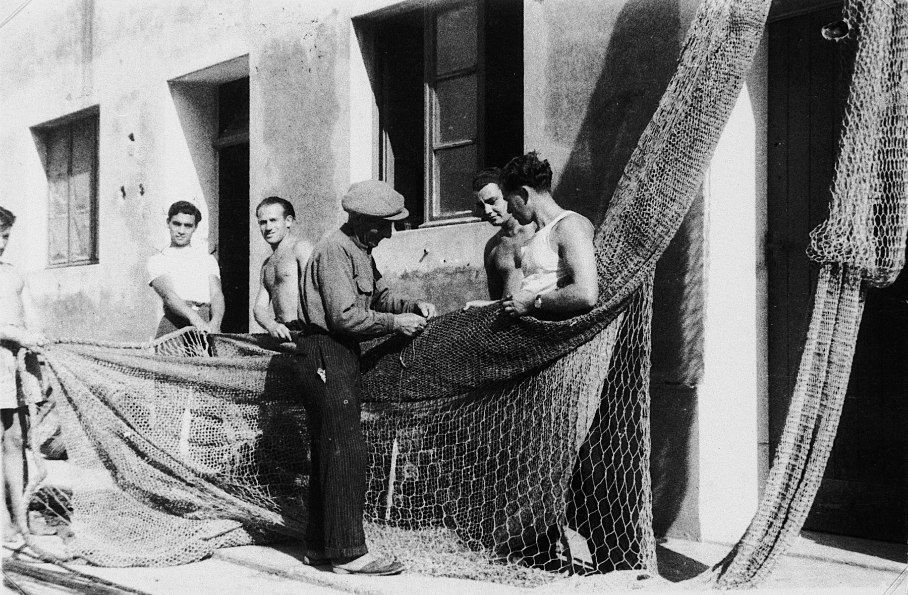 An Italian instructor, Meletti Fano, demonstrates how to fix fishing nets to four Jewish DPs at the Migdalor hachshara, a maritime Zionist collective in Fano, Italy.