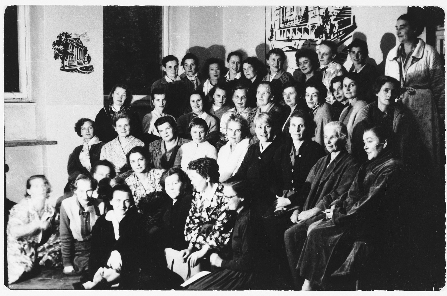 Group portrait of Polish female survivors of medical experimentations at the Ravensbrueck concentration camp in a medical clinic in Warsaw, where they are undergoing examinations by Polish physicians and Dr. Hitzig from the United States.