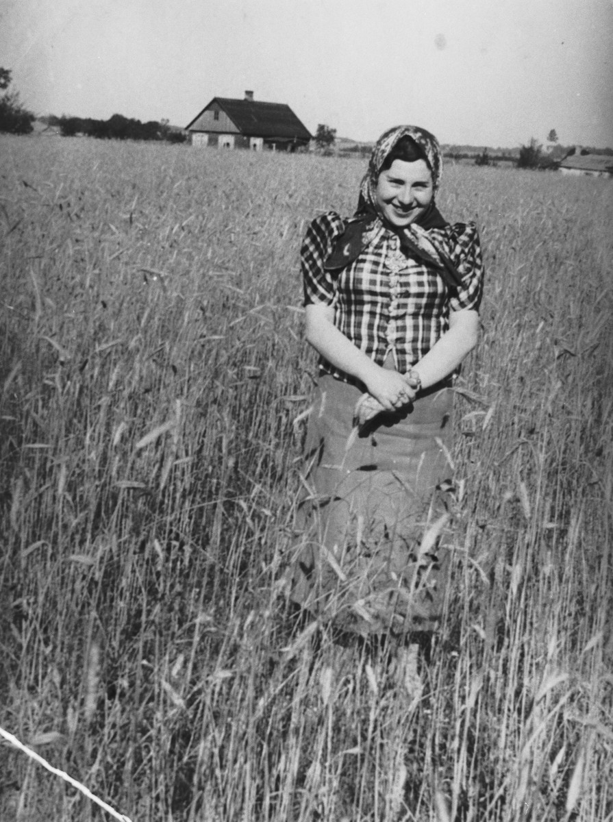 Ita Grynberg stands in a wheat field near her parents' house.  She was later killed while hiding with her nephew in the village of Glowaczce.