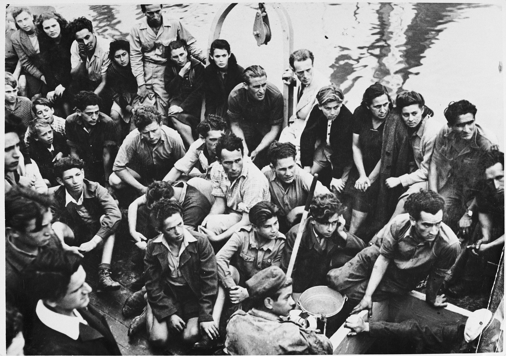 Jewish DPs who are members of the Migdalor hachshara, a maritime Zionist collective in Fano, Italy, crowd on the deck of a fishing boat.  Among those pictured are Kozik (bottom, left); middle row (right to left): Sevek, unknown, Zucker. and Vladek.  Top row (right to left): Daniel Sarchuk, Sigmund Zelig Braun, Eshter Nessel, her mother, unknown, Yaakov Neihof, Patt, Rusha, Zlatka, Karol, Roza, Yidl, Leah Rosenberg, and Chana Beler.