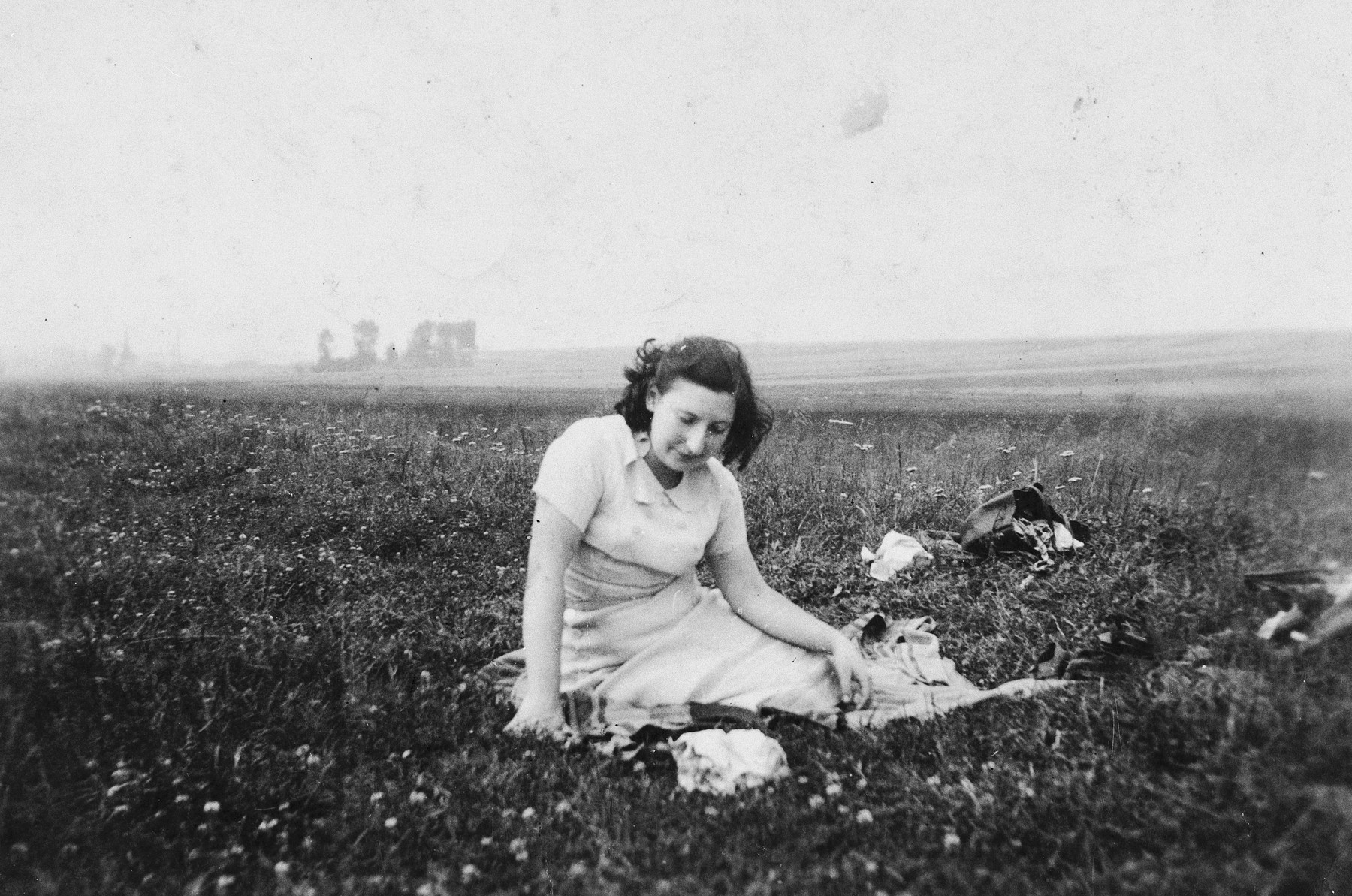 A young woman sits in a field of grass in the Dabrowa Gornicza ghetto.  Pictured is Fela Szeps.