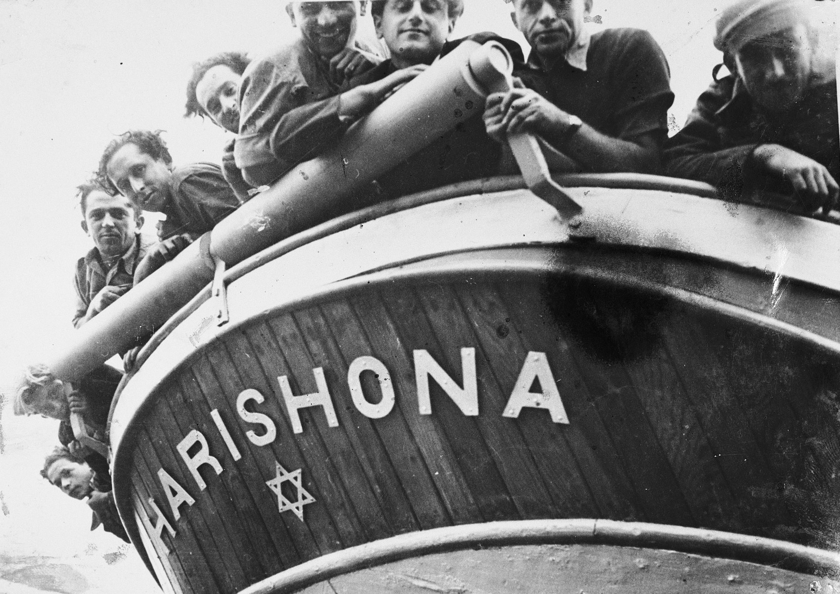 Jewish DPs look over the bow of their newly constructed fishing boat at the Migdalor hachshara, a maritime Zionist collective in Fano, Italy.  Among those pictured from right to left are: Yitzhak Goldhammer, Laufer, Kotzchik, Yuzek Kempler, Sevek and Patt.