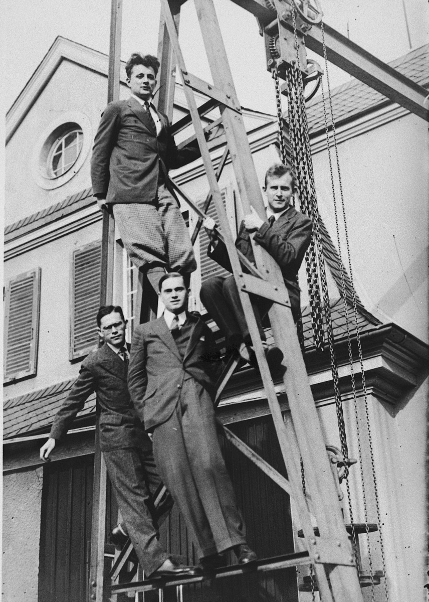 A group of young scientists from the Kaiser Wilhelm Institute pose on the scaffolding outside the institute.  Front row (left to right) Ladislaus Farkas and Adalbert Farkas.  Above them are Paul Harteck and K.E. Bonhoeffer.  The latter two were not Jewish.