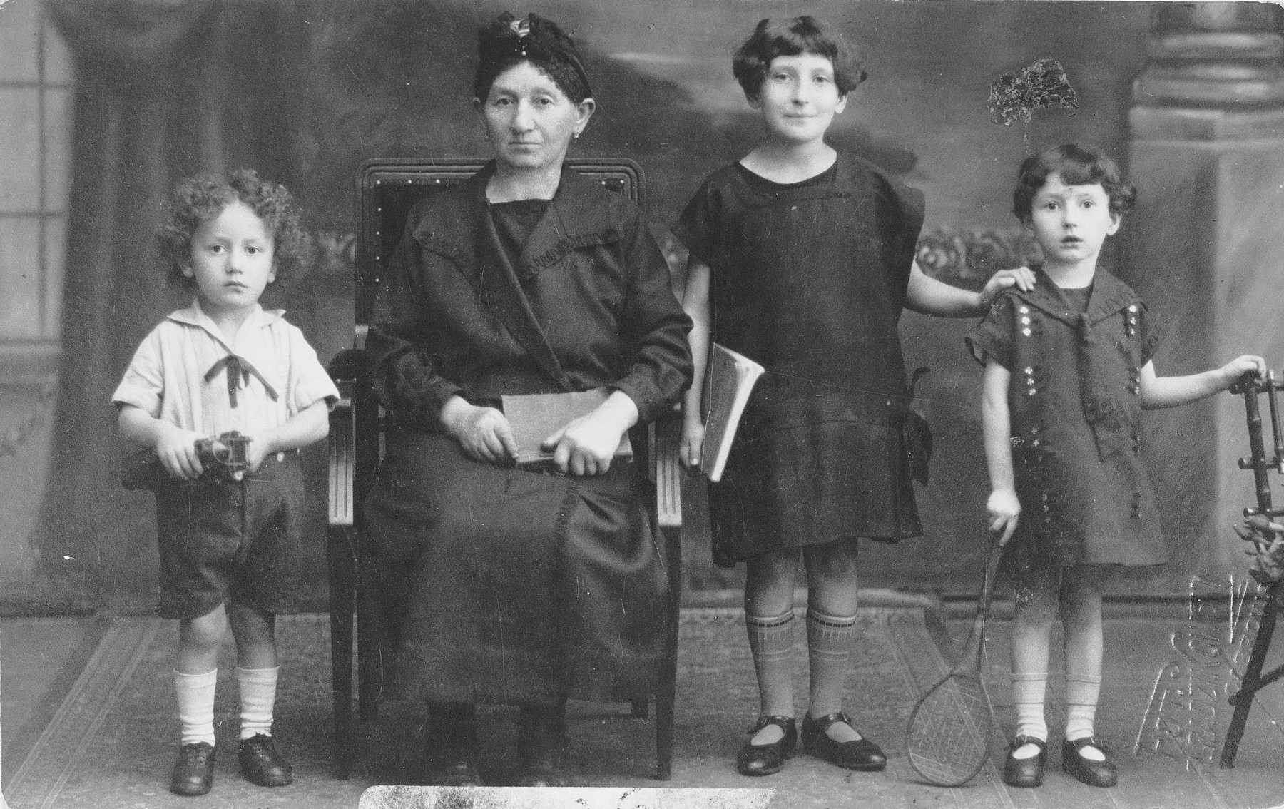 Studio portrait of three Jewish children with their grandmother in Dabrowa Gornicza, Poland.  Pictured from left to right are: Moniek, his grandmother (name unknown), Fela and Sabina Szeps.