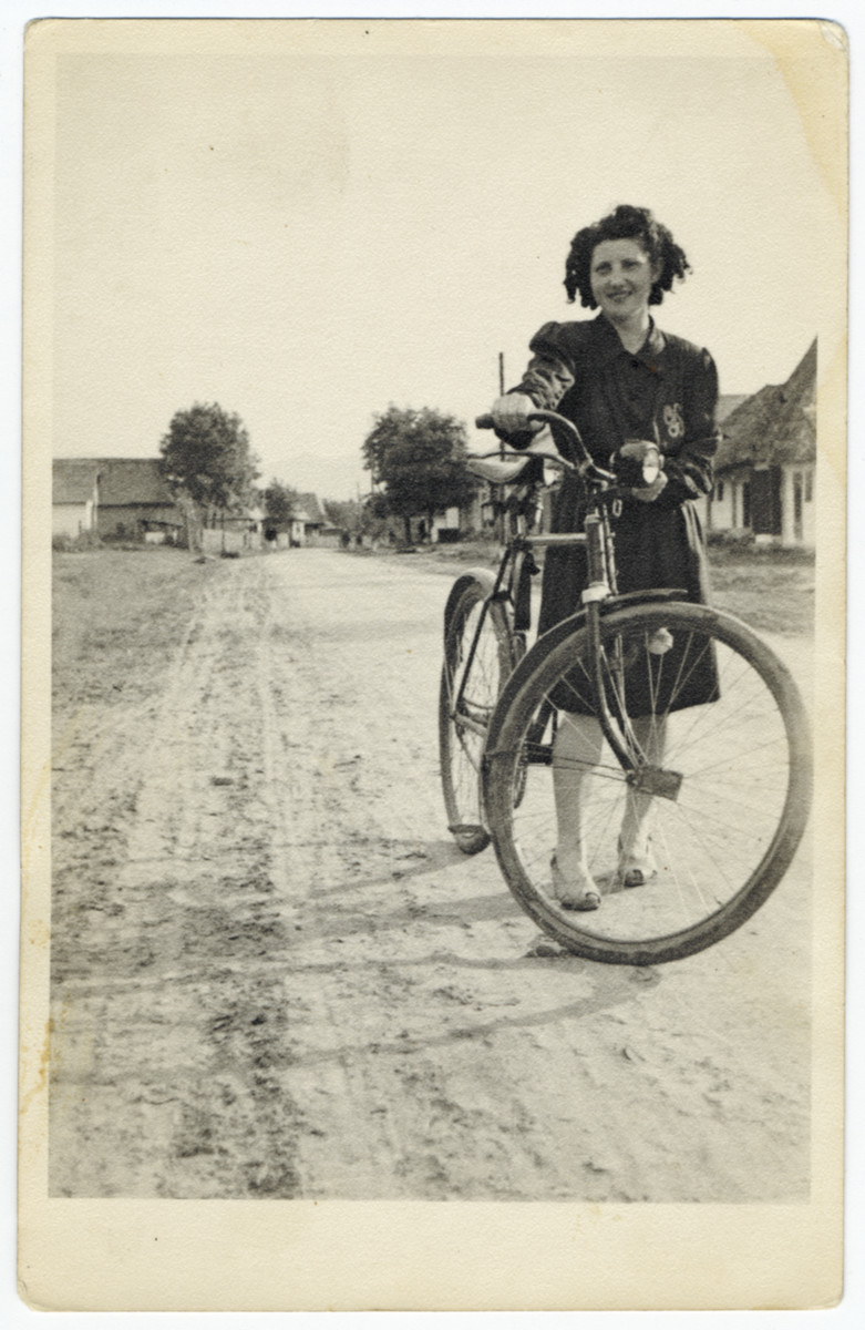 A young Jewish woman stands next to her bicycle on a street in Vonihovo.  Pictured is Suri Ganz.