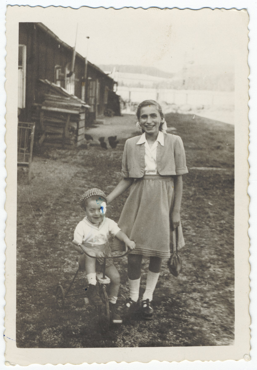 A young boy rides his tricycle next to his older sister in the Hallein displaced persons' camp.  Pictured are Yakov and Eva Freedman.