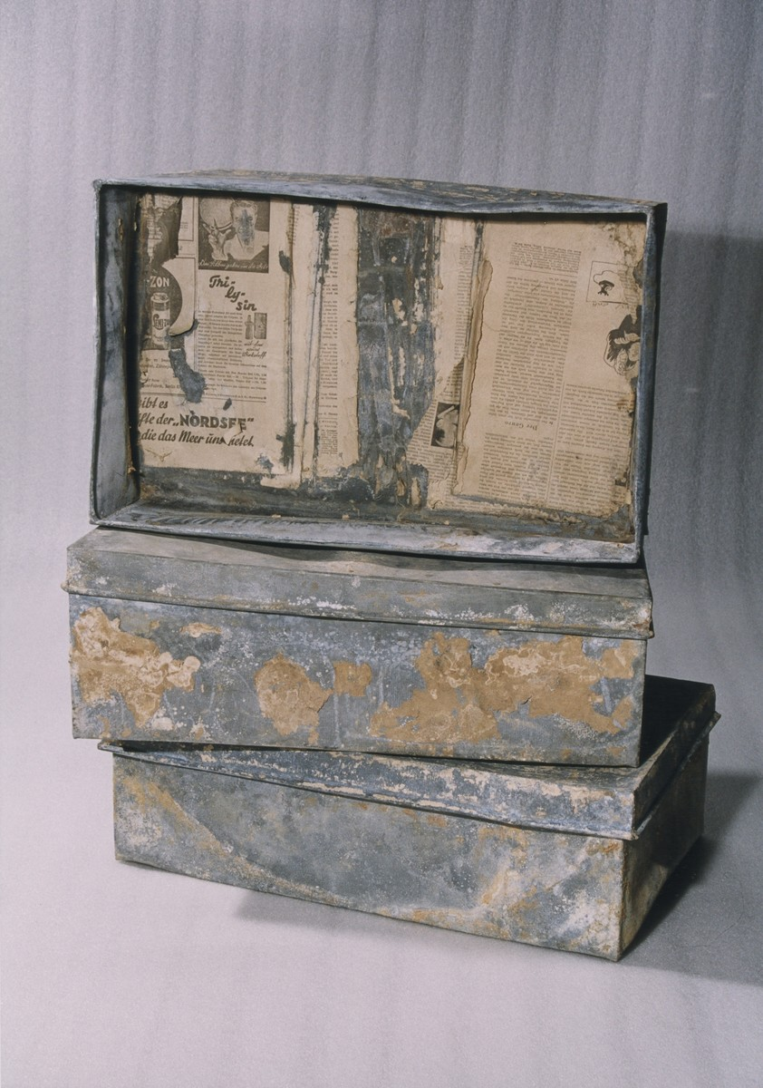 Three of the ten metal boxes in which portions of the Ringelblum Oneg Shabbat archives were hidden and buried in the Warsaw ghetto.  The boxes are currently in the possession of the Jewish Historical Institute in Warsaw.  In this view the boxes are piled on top of one another.  The box on top is displayed on its side without the lid.