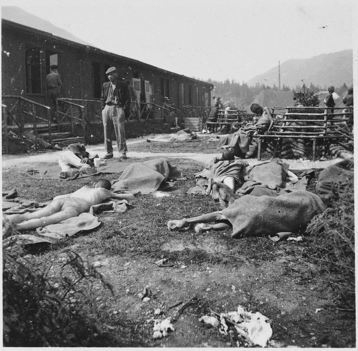 Survivors lie outside among the dead at the newly liberated Ebensee concentration camp.