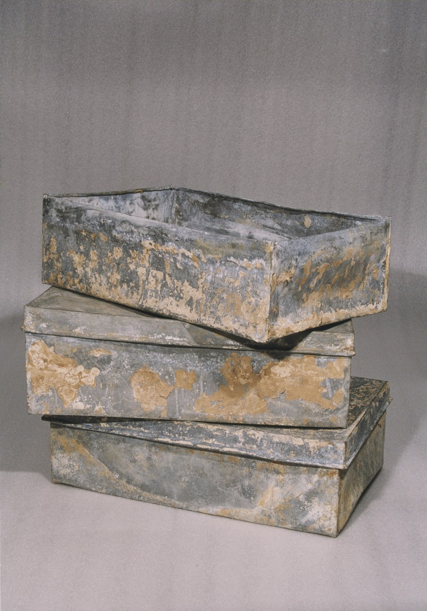 Three of the ten metal boxes in which portions of the Ringelblum Oneg Shabbat archives were hidden and buried in the Warsaw ghetto.  The boxes are currently in the possession of the Jewish Historical Institute in Warsaw.  In this view the boxes are piled on top of one another.  The box on top is displayed without the lid.