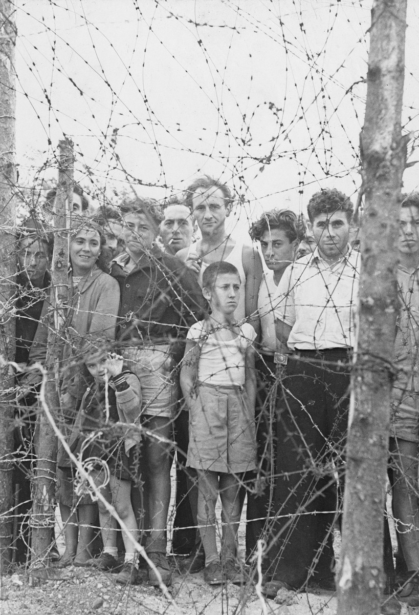 A group of former Exodus 1947 passengers stand behind the barbed wire enclosure at the Poppendorf displaced persons camp in Germany.