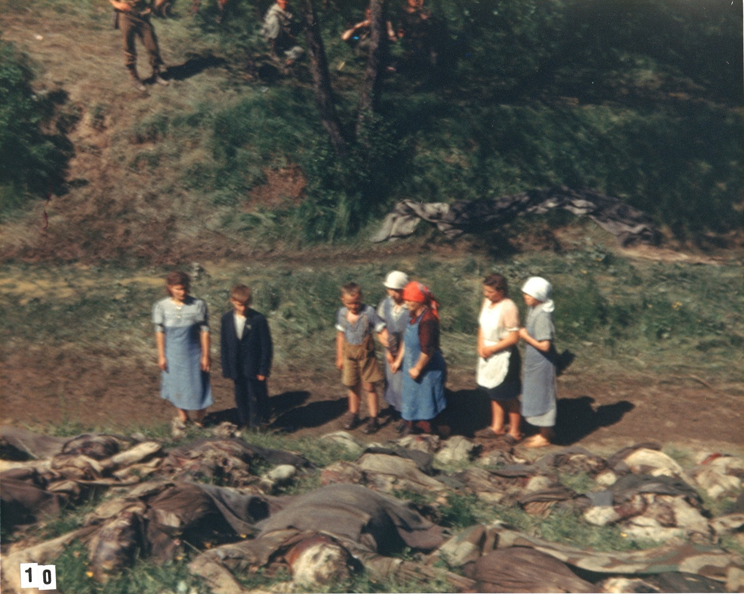 German civilians walk among the corpses of prisoners exhumed from a mass grave near the town of Nammering.