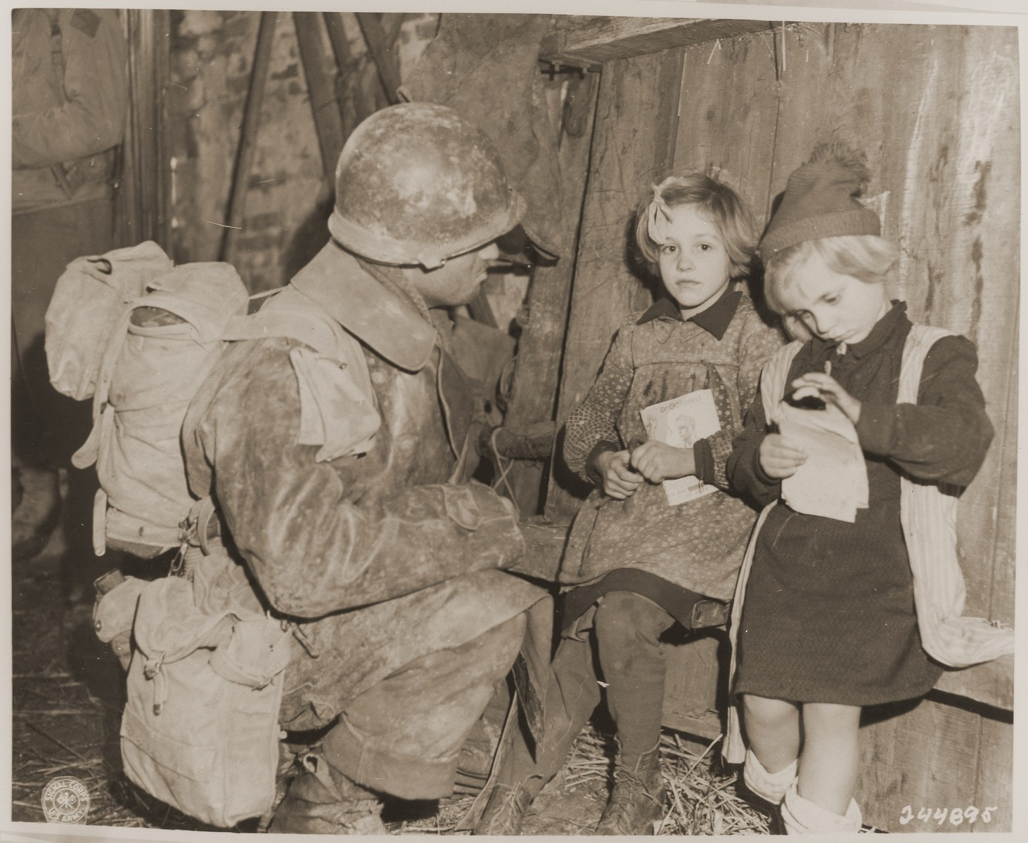 Louis Kolokoff, of the 101st Infantry Regiment, 26th Division, talks to two French girls who are holding Goebbels literature.