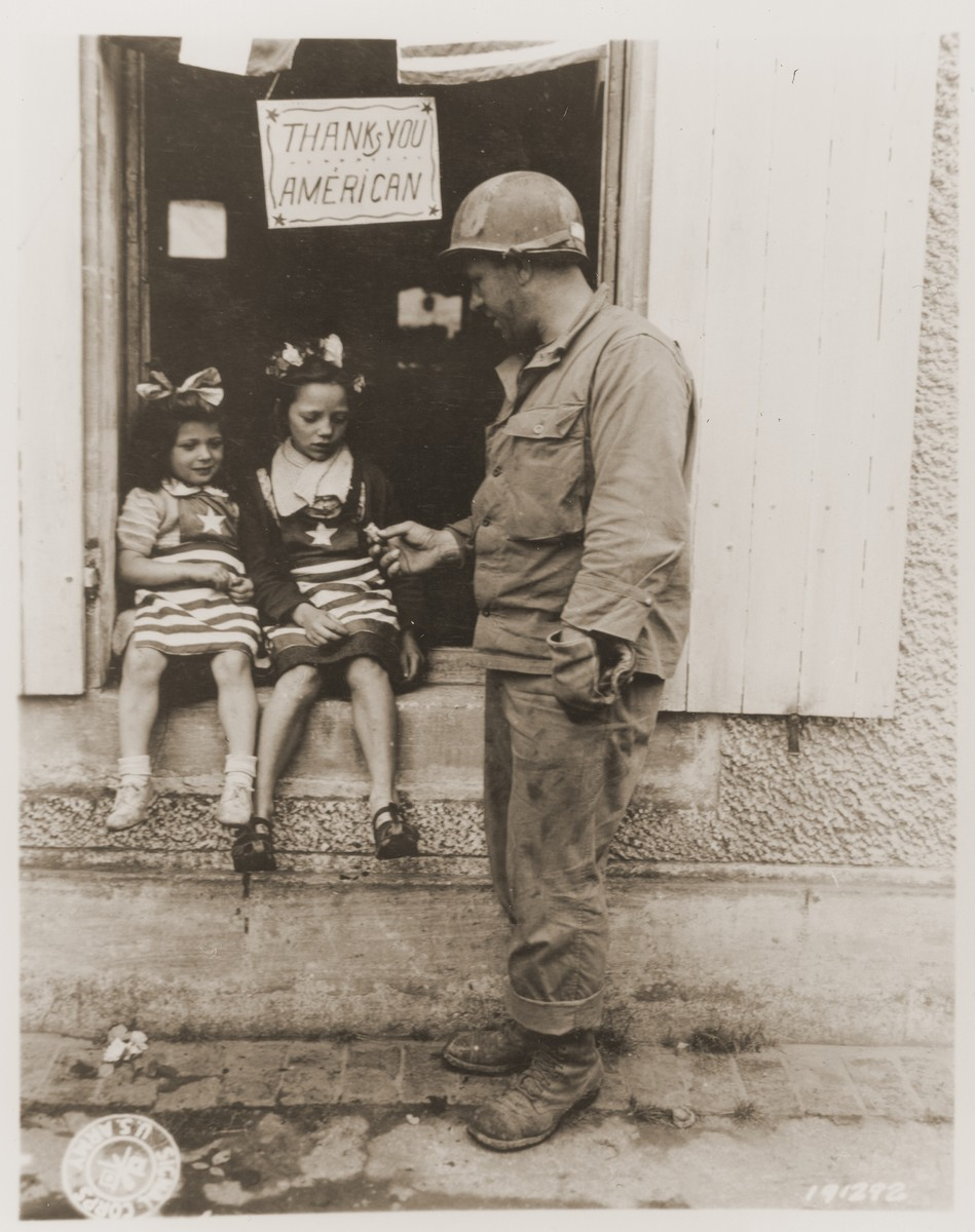 Sgt. Walter P. Goworek gives G.I. candy to two French girls, who are wearing costumes for a Fourth of July observance in La Mine.