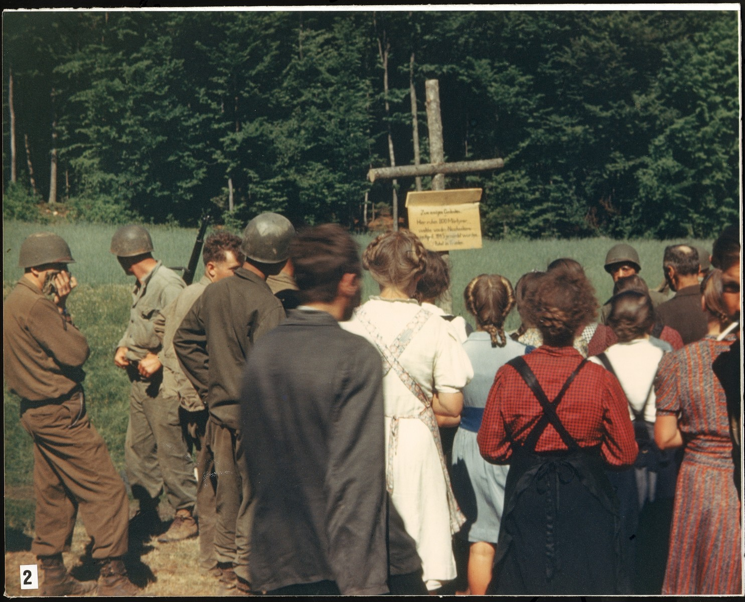 Under the direction of American soldiers, German civilians are forced to read the sign erected by the U.S. Army to mark the site of the Nammering atrocity.