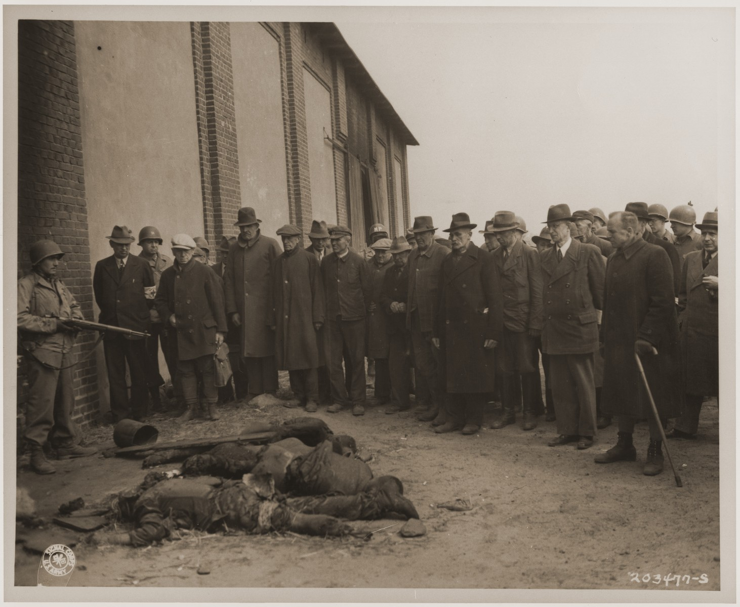 Under the supervision of American soldiers, mayors and townspeople from Gardelegen and other surrounding towns are forced to view the charred corpses of prisoners shot while trying to escape a burning barn.