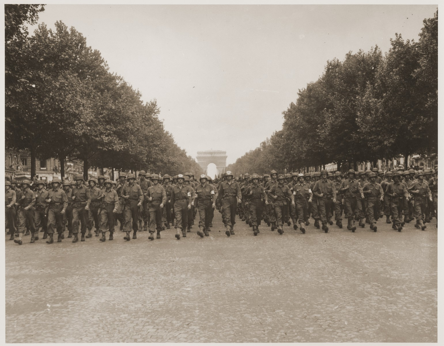 American troops of the 28th Infantry Division march down the Champs Elysees, Paris, in a victory parade.