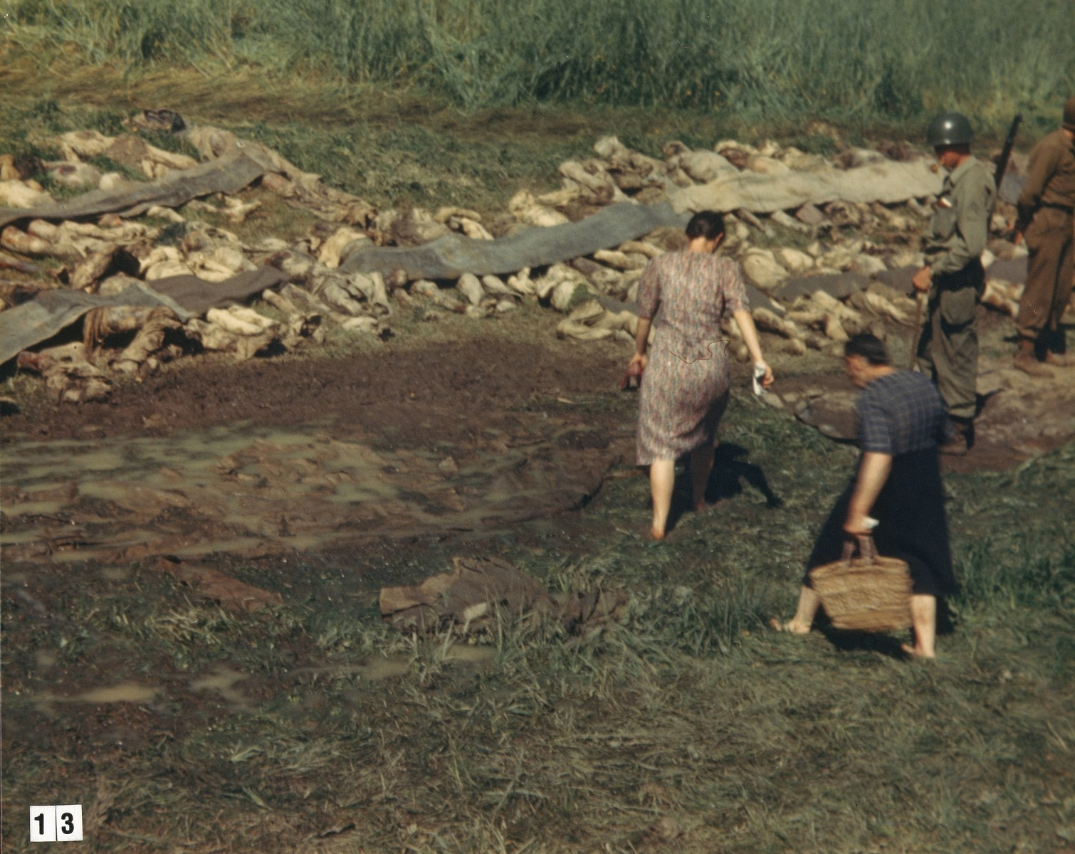 Bare-footed German women are forced by American soldiers to walk among the corpses of prisoners exhumed from a mass grave near Nammering.    [The women might have been forced to take off their shoes by U.S. troops so they would walk through the mud near the grave.]