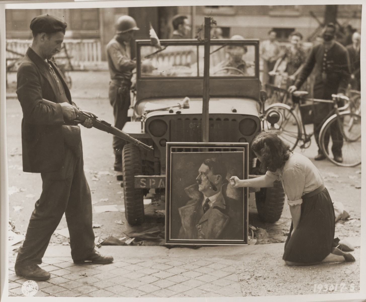 A French civilian and a French resistance fighter deface a portrait of Adolf Hitler.