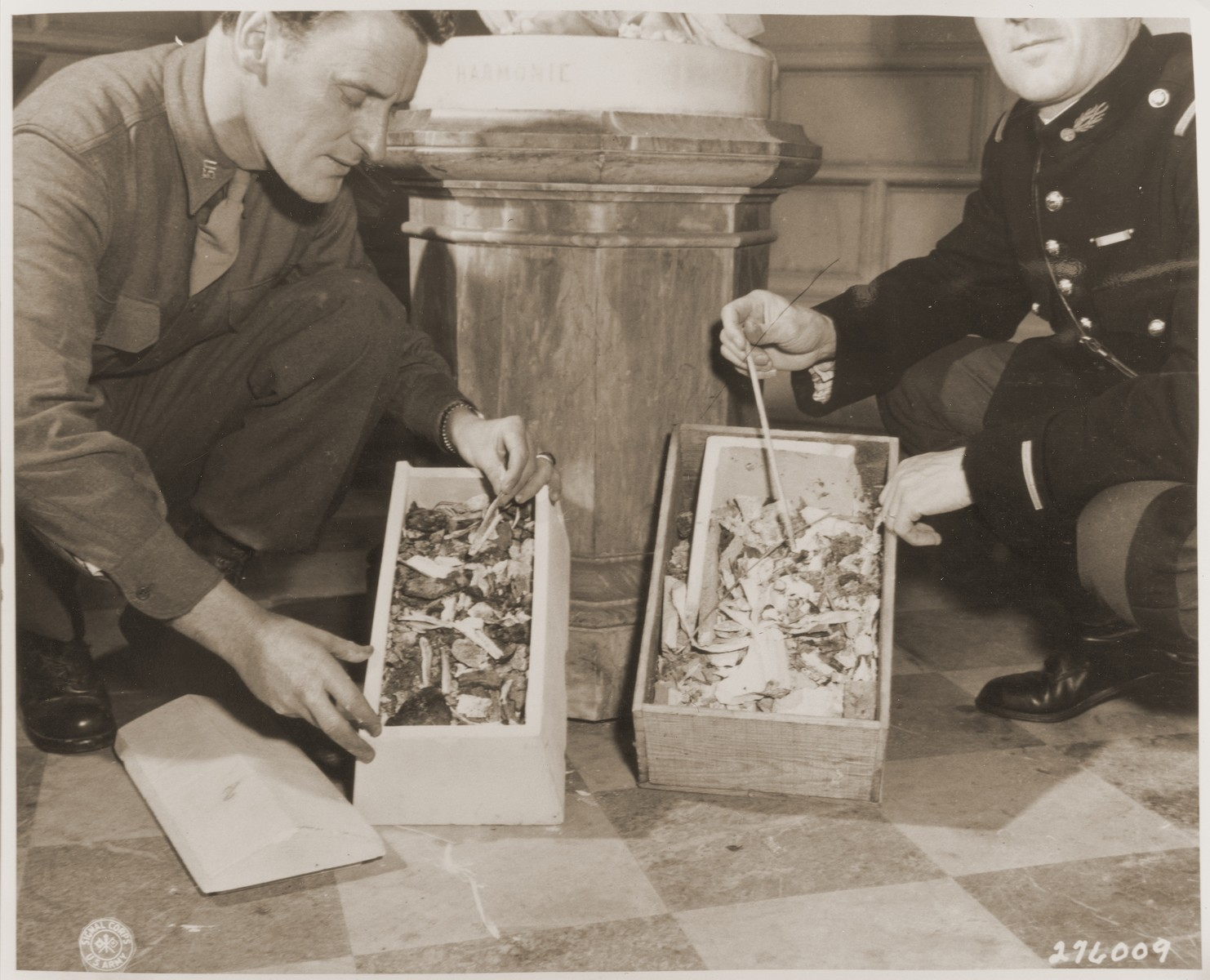 An American and a French soldier examine boxes containing the remains of human bones taken from the incinerator at the German Gestapo headquarters building in Paris.