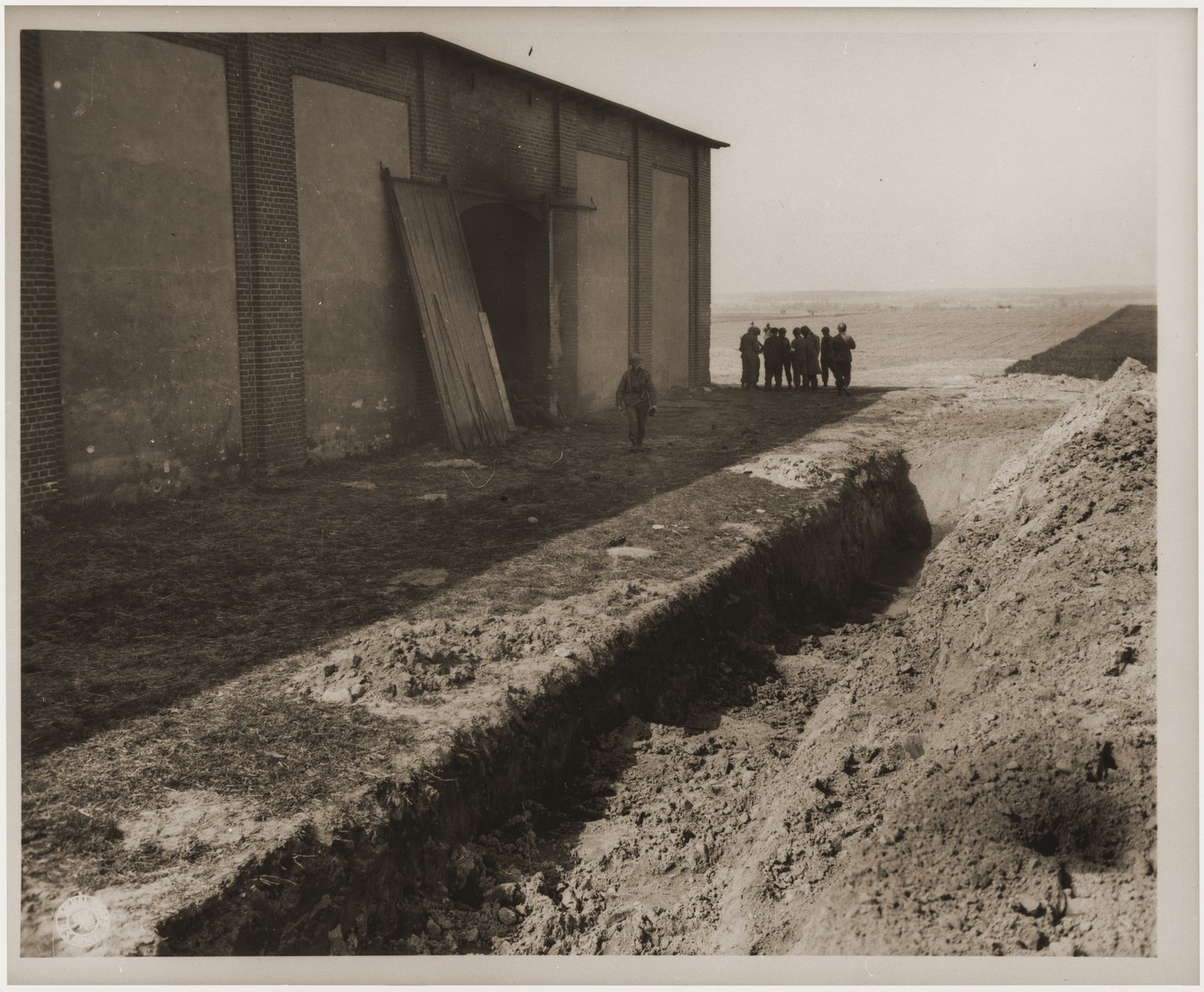 A partially filled mass grave lies in the foreground as American soldiers walk around a barn outside of Gardelegen in which over 1,000 prisoners were burned alive by the SS.