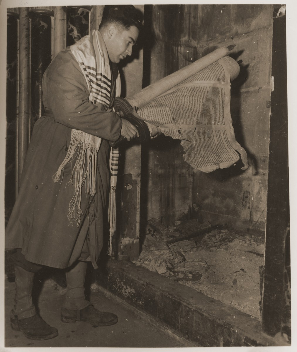 U.S. Army chaplain Herman Dicker from Brooklyn, N.Y., examines a damaged Torah scroll in the ark of the destroyed synagogue in Metz.