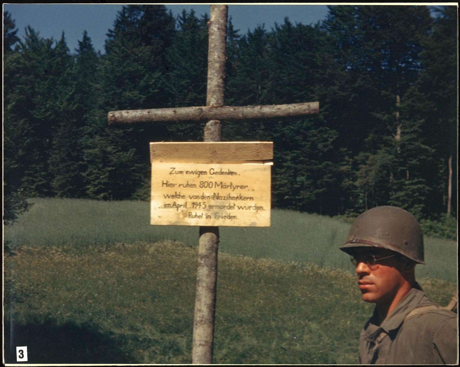 """An American soldier stands next to a sign erected by the U.S. Army to mark the site of the Nammering atrocity.  It reads: """"In eternal memory.  Here lie 800 martyrs who were murdered by Nazi executioners in April 1945.  Rest in peace."""""""