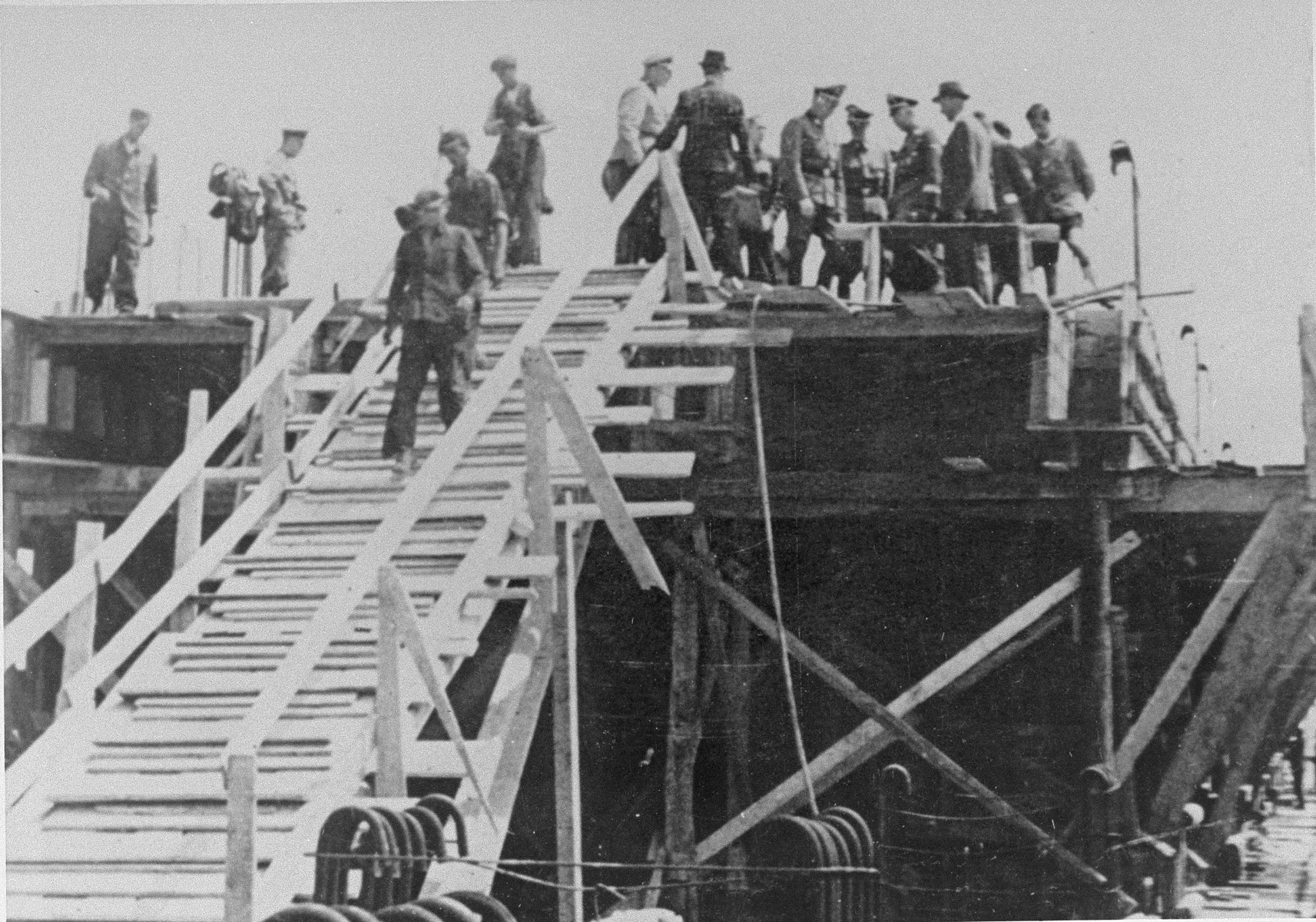 Reichsfuehrer SS Heinrich Himmler stands alongside Max Faust (wearing the fedora) on the upper floor of a partially constructed building, during a tour of the Monowitz-Buna building site.  Faust, who was an IG Farben engineer, was the head of building operations at Monowitz-Buna.