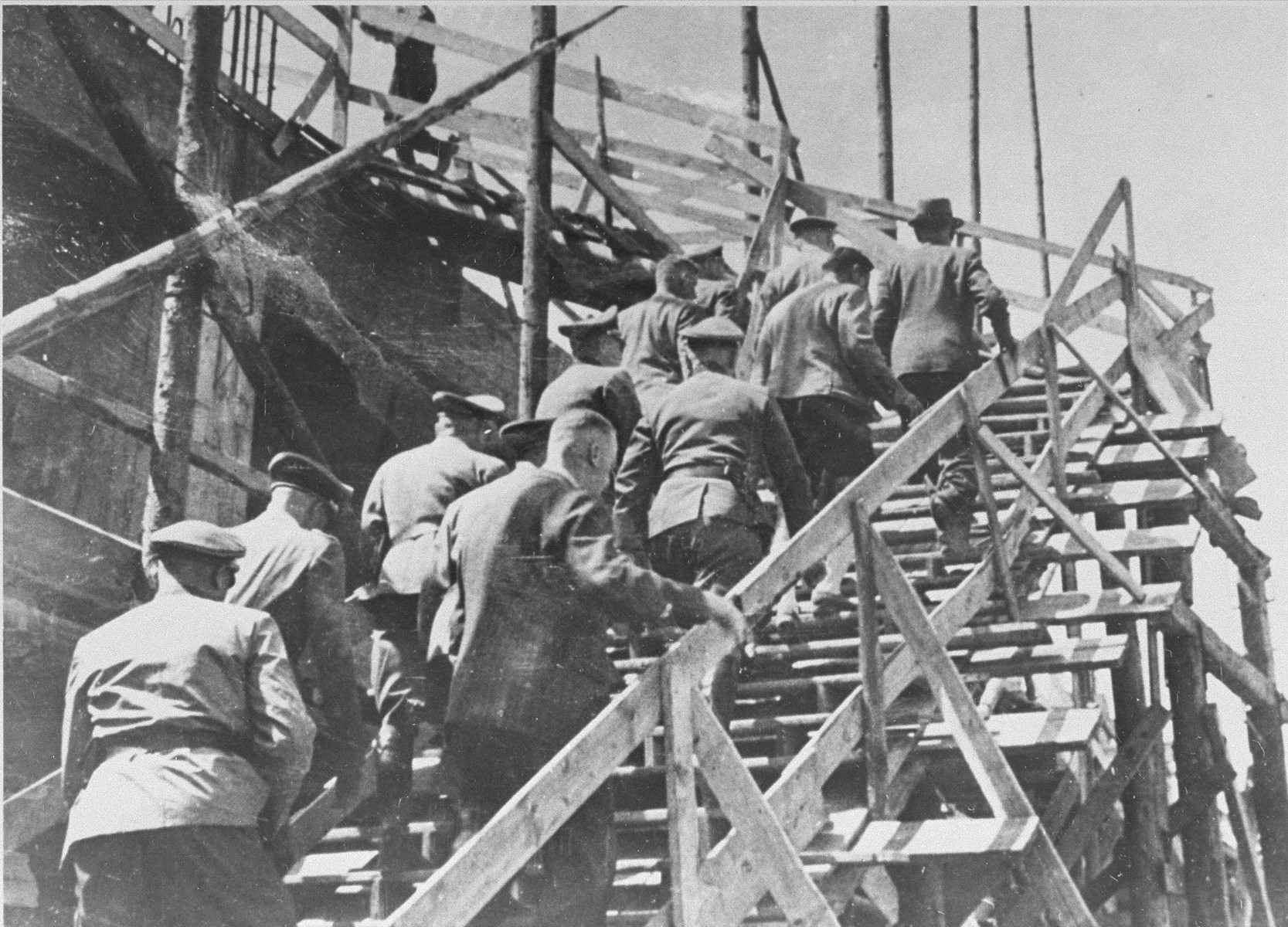 Reichsfuehrer SS Heinrich Himmler (top left) climbs a wooden staircase during a tour of the Monowitz-Buna building site in the company of Max Faust (top right).   Faust, who was an IG Farben engineer, was the head of building operations at Monowitz-Buna.