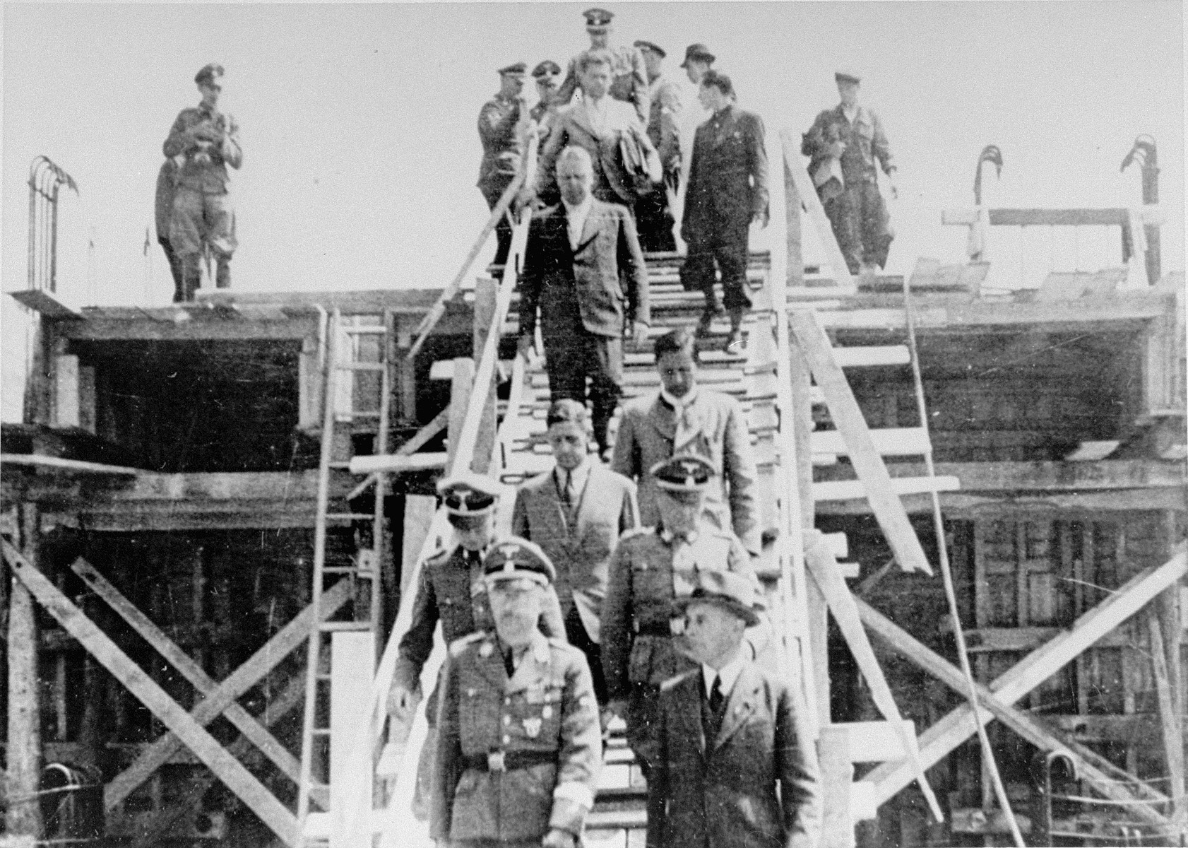 Reichsfuehrer SS Heinrich Himmler (bottom left) descends a wooden staircase during a tour of the Monowitz-Buna building site in the company of Max Faust (bottom right).   Faust, who was an IG Farben engineer, was the head of building operations at Monowitz-Buna.