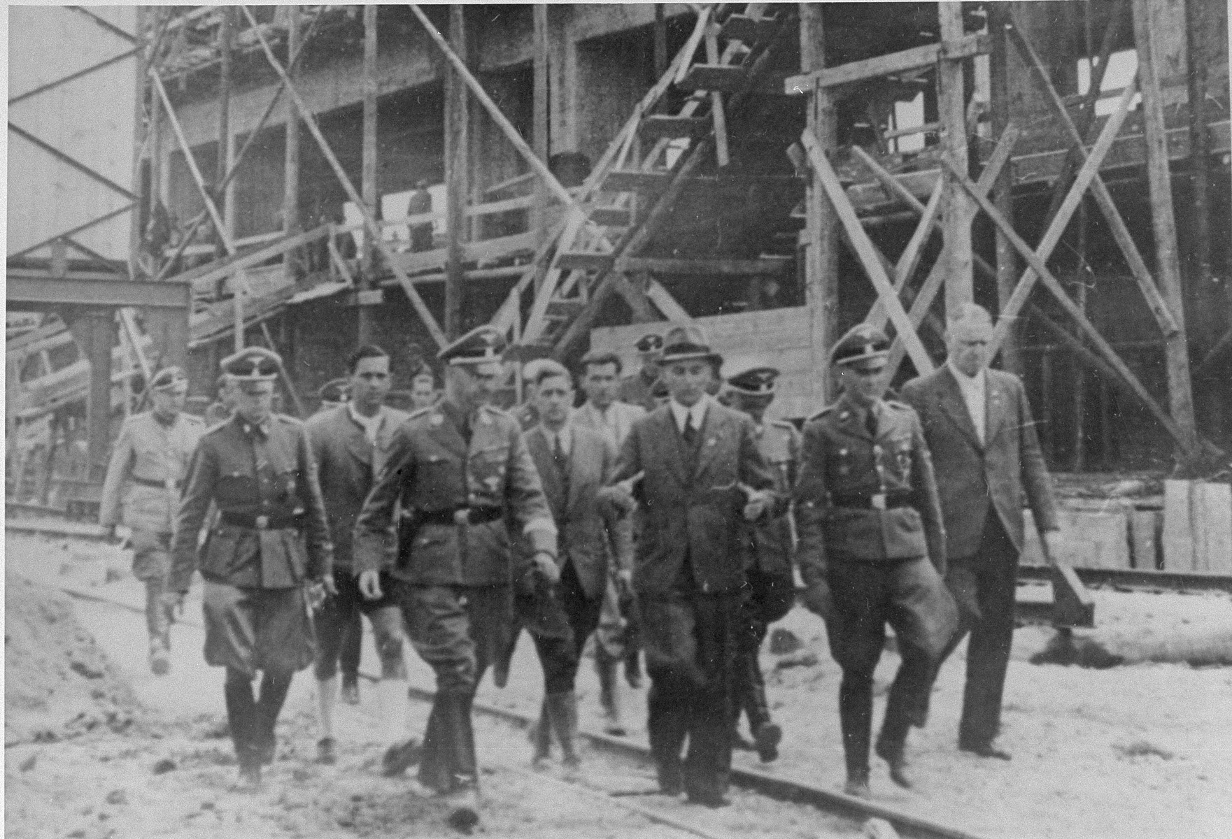 Reichsfuehrer SS Heinrich Himmler tours the Monowitz-Buna building site in the company of SS officers and IG Farben engineers.   Among those pictured are: Rudolf Brandt (left, in SS uniform slightly behind Himmler), Heinrich Himmler, Max Faust (wearing the fedora) and Rudolf Hoess (next to Faust).  Faust, who was an IG Farben engineer, was the head of building operations at Monowitz-Buna.
