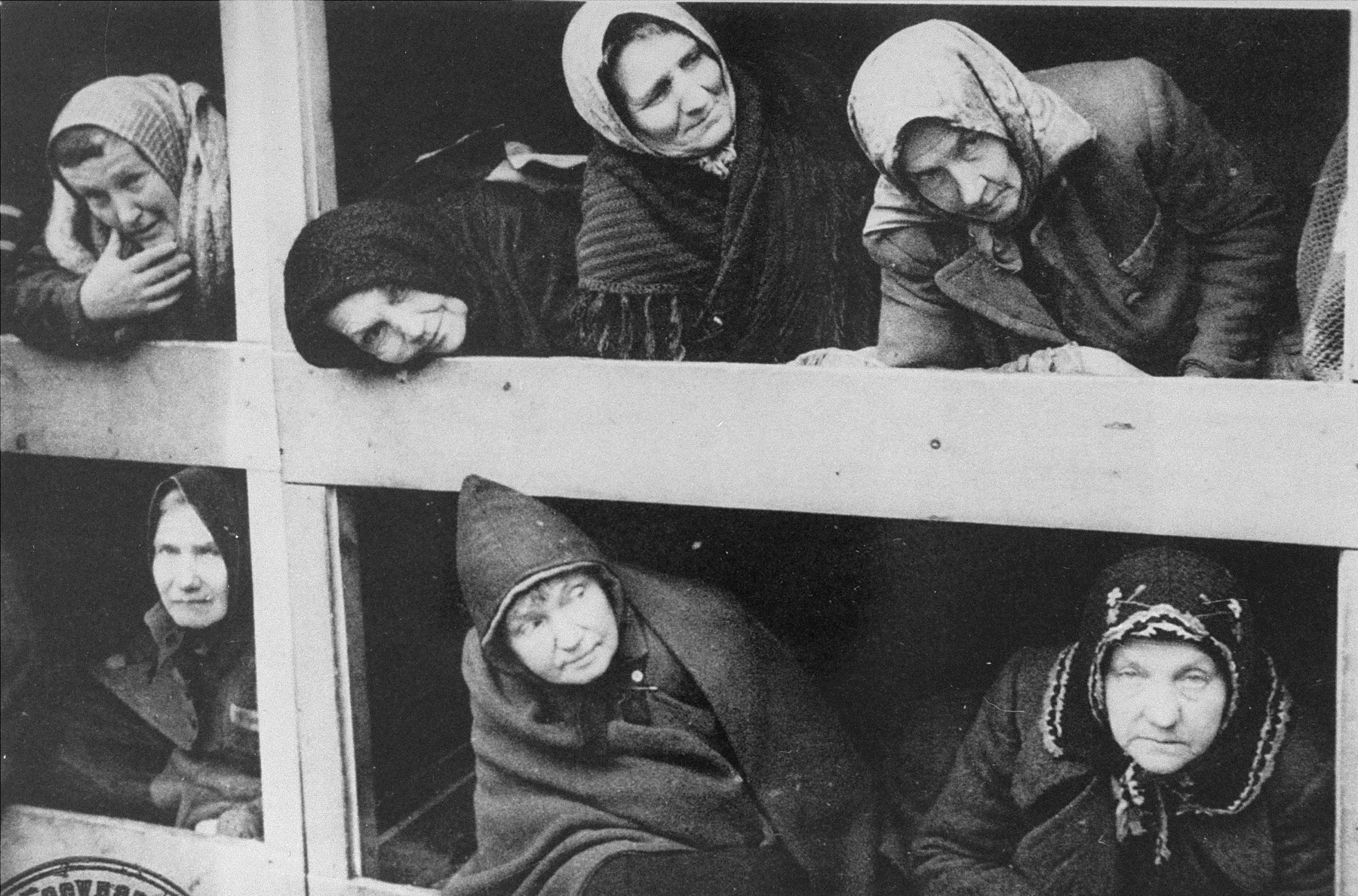 Former women-prisoners on the wooden bunks that served as beds, in Auschwitz concentration camp.  STILL PHOTOGRAPH FROM THE SOVIET FILM of the liberation of Auschwitz, taken by the film unit of the First Ukrainian Front.