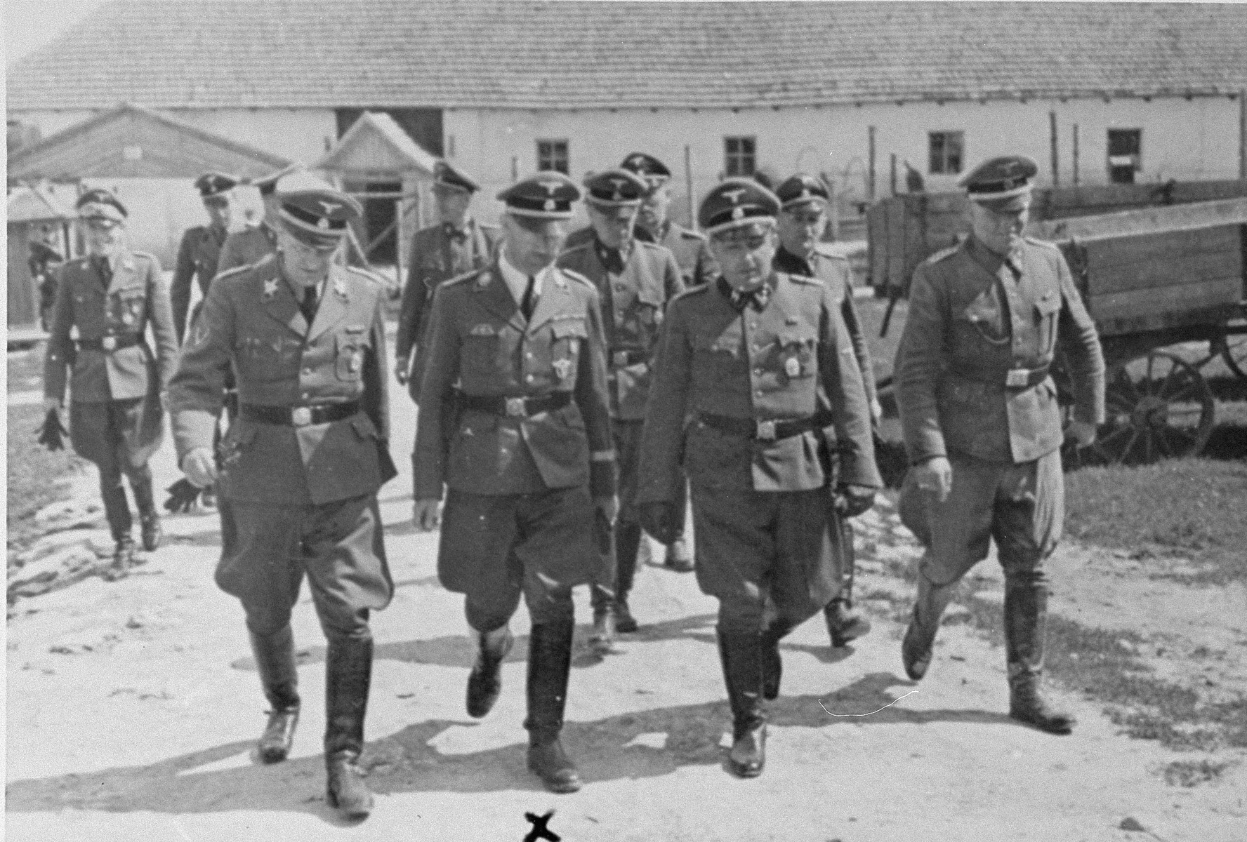 Reichsfuehrer SS Heinrich Himmler tours a Jewish labor camp in Galicia along the main supply route in the company of camp commandant, Friedrich Warzok.  Pictured in the front row from left to right are: Johannes Jost, Heinrich Himmler, Friedrich Warzok.  Also pictured are Josef Kirmaier (between Himmler and Warzok in the second row) and Fritz Katzmann (second row, left).