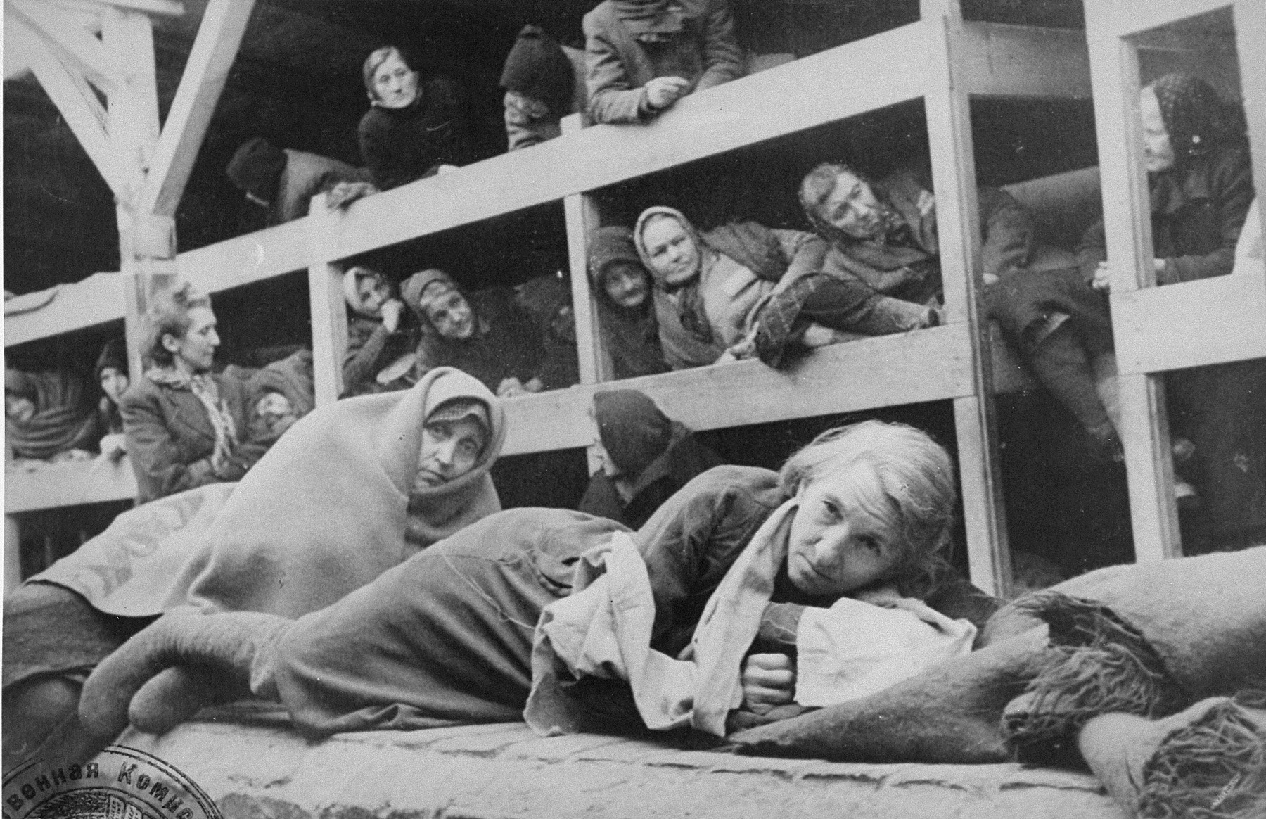 Women in the barracks of the newly liberated Auschwitz concentration camp.  Pictured on the far left, wearing a scarf, is Rivka Ruchle Chencinska (nee Krause).  STILL PHOTOGRAPH FROM THE SOVIET FILM of the liberation of Auschwitz, taken by the film unit of the First Ukrainian Front.