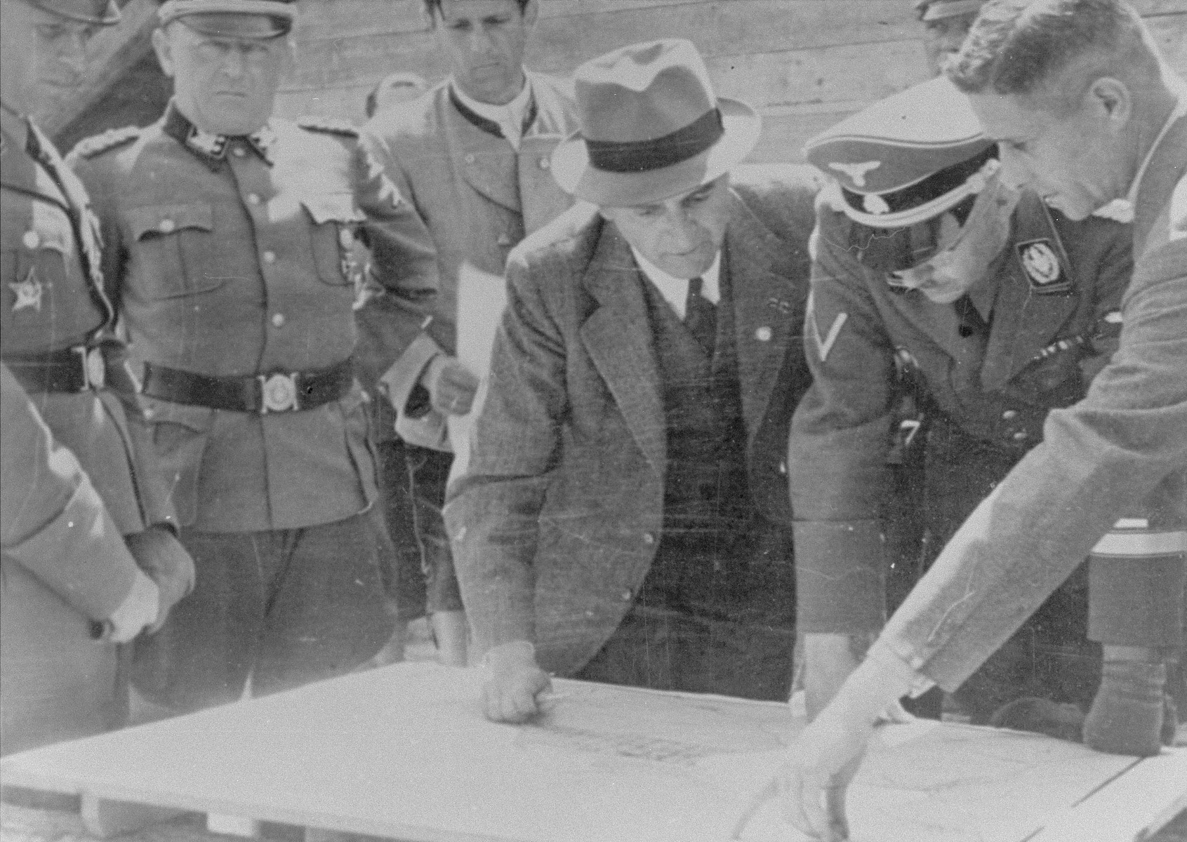 Reichsfuehrer SS Heinrich Himmler examines a building plan with Max Faust (wearing the fedora) during an inspection tour of the Monowitz-Buna building site.  Faust, who was an IG Farben engineer, was the head of building operations at Monowitz-Buna.  Also pictured is SS Obergruppenfuehrer Ernst Schmauser (second from the left) and Josef Kiermaier (behind Himmler, partially hidden from view)