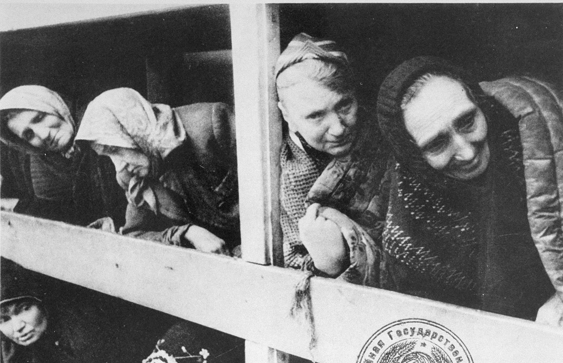 Former women-prisoners on the wooden bunks that served as beds, in Auschwitz concentration camp.   STILL PHOTOGRAPH FROM THE SOVIET FILM of the liberation of Auschwitz, taken by the film unit of the First Ukrainian Front.  One of the woman has been identified as Rivka Ruchle nee Krause.Wysoki.