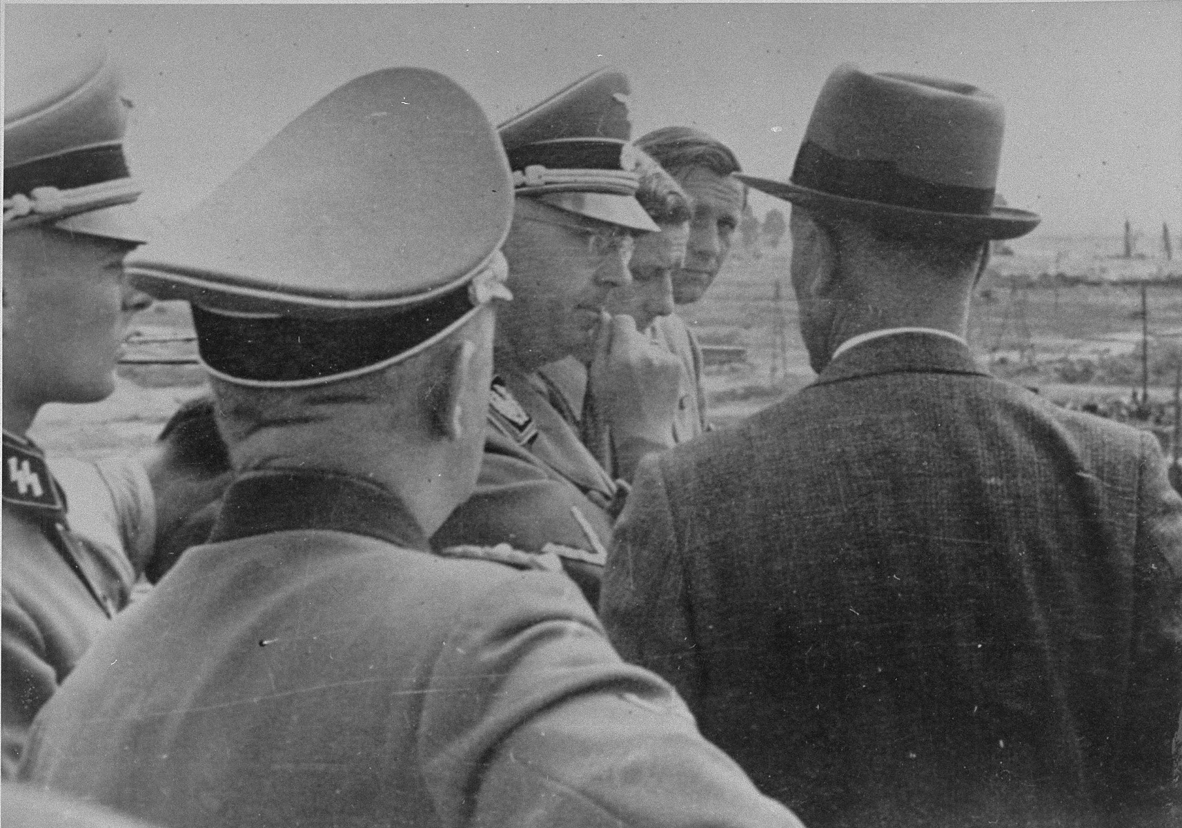 Reichsfuehrer SS Heinrich Himmler converses with Max Faust (wearing the fedora) during a tour of the Monowitz-Buna building site. The SS officer to the left is Werner Grothmann.    Faust, who was an IG Farben engineer, was the head of building operations at Monowitz-Buna.