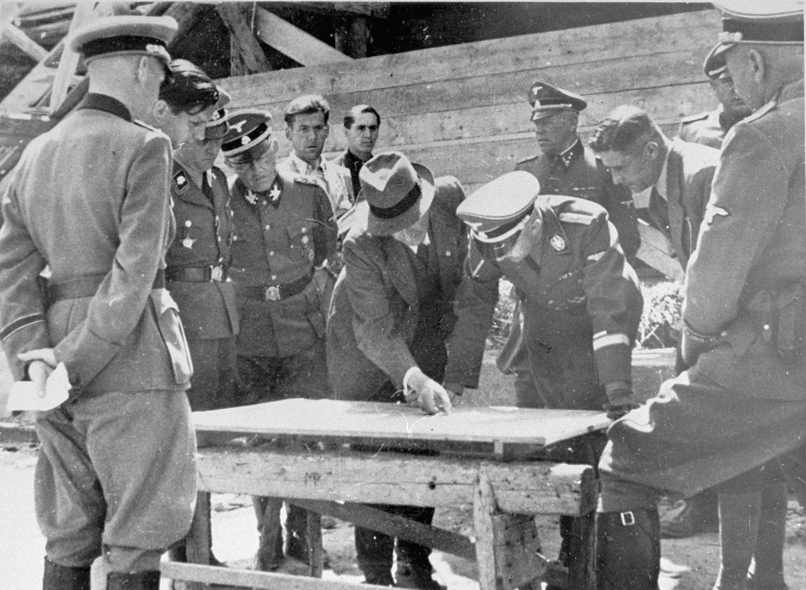 Reichsfuehrer SS Heinrich Himmler examines a building plan with Max Faust (wearing the fedora) during an inspection tour of the Monowitz-Buna building site.  Faust, who was an IG Farben engineer, was the head of building operations at Monowitz-Buna.  Individuals pictured third and fourth from the left have been identified as SS-Obersturmbannfuehrer Rudolf Hoess (Lagerkommandant, KL-Auschwitz), and SS-Obergruppenfuehrer and General der Polizei Ernst Heinrich Schmauser (Hoeherer SS- and Polizeifuehrer Suedost).