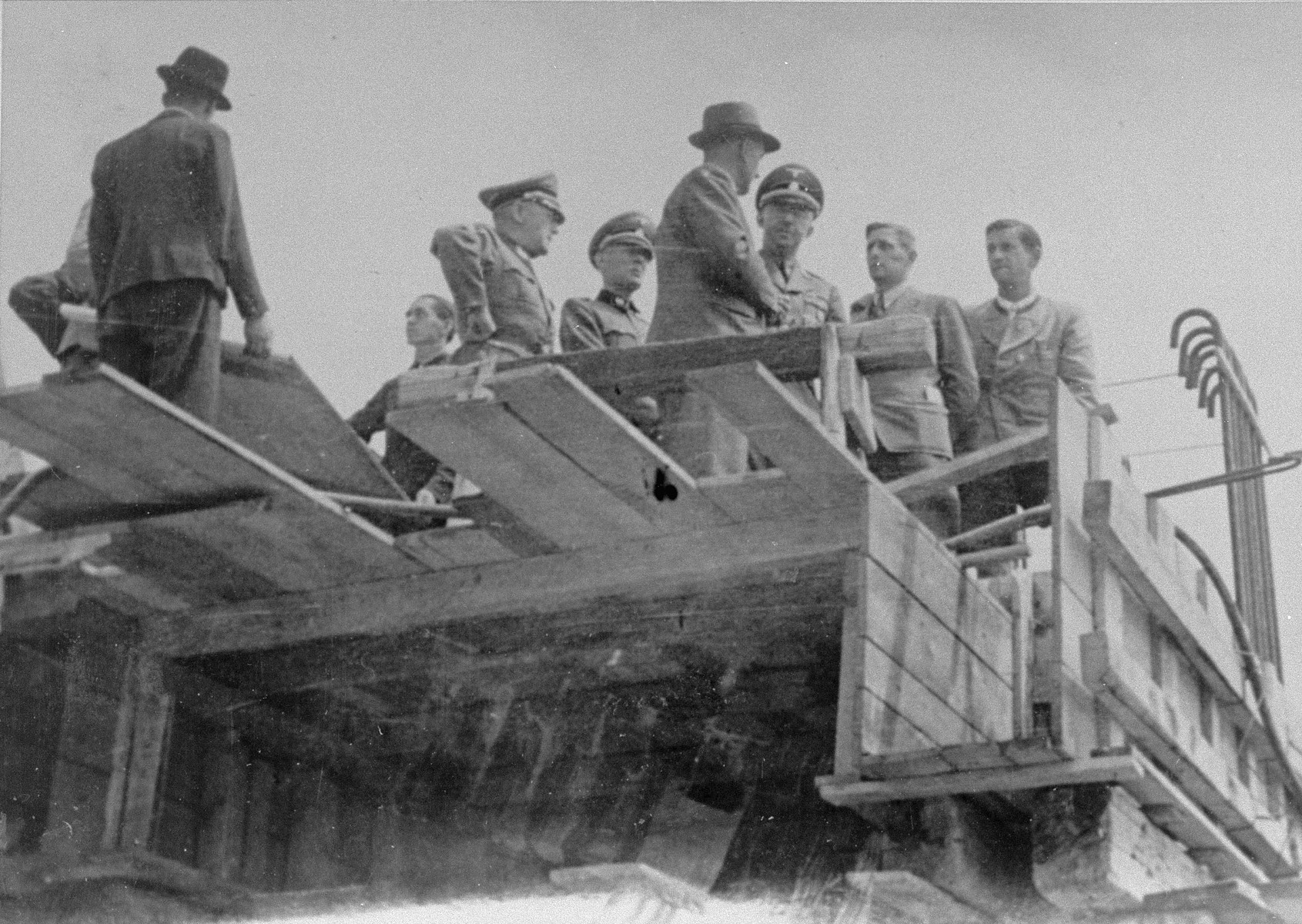 Reichsfuehrer SS Heinrich Himmler converses with Max Faust (wearing the fedora) on the upper floor of a partially constructed building, during a tour of the Monowitz-Buna building site.   Faust, who was an IG Farben engineer, was the head of building operations at Monowitz-Buna.