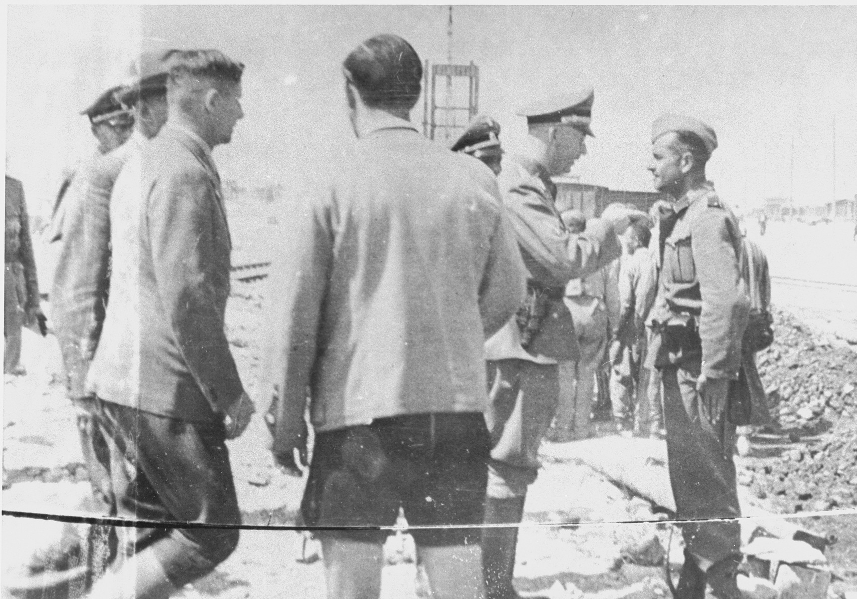 During a tour of the Monowitz-Buna building site, Reichsfuehrer SS Heinrich Himmler speaks to a member of the SS who is supervising the prisoners working on the construction of the IG Farben plant.