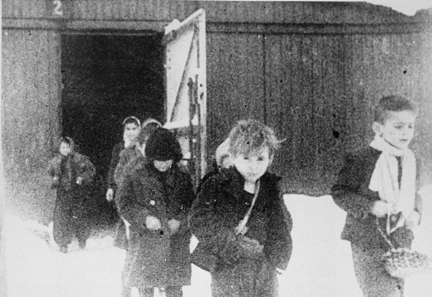 Child survivors walk out of the children's barracks in Auschwitz.  STILL PHOTOGRAPH FROM THE SOVIET FILM of the liberation of Auschwitz, taken by the film unit of the First Ukrainian Front.