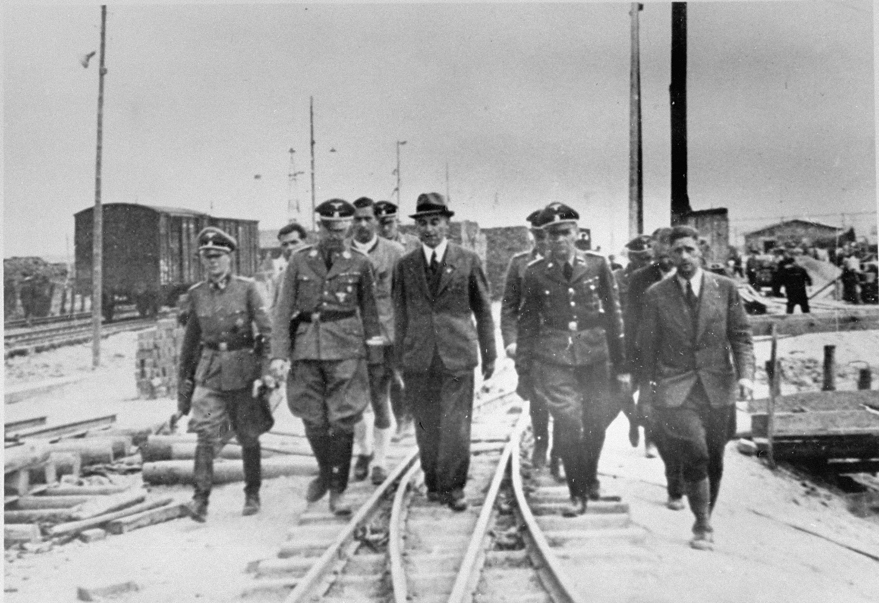 Reichsfuehrer SS Heinrich Himmler tours the Monowitz-Buna building site in the company of SS officers and IG Farben engineers.   Pictured in the front row from left to right are: Rudolf Brandt, Heinrich Himmler, Max Faust, and Rudolf Hoess.  Faust, who was an IG Farben engineer, was the head of building operations at Monowitz-Buna.