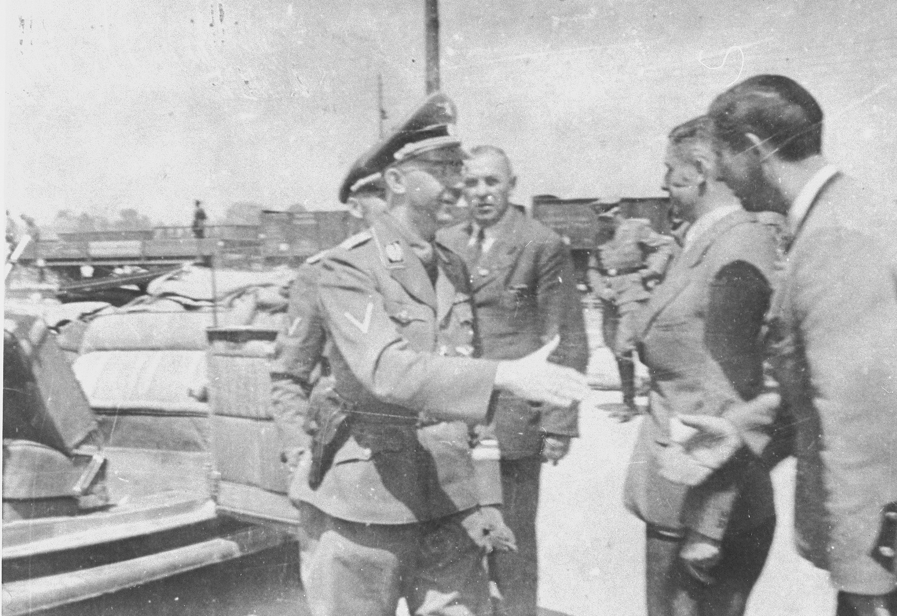 During a tour of the Monowitz-Buna building site, Reichsfuehrer SS Heinrich Himmler extends his hand in greeting to the engineers supervising the construction.