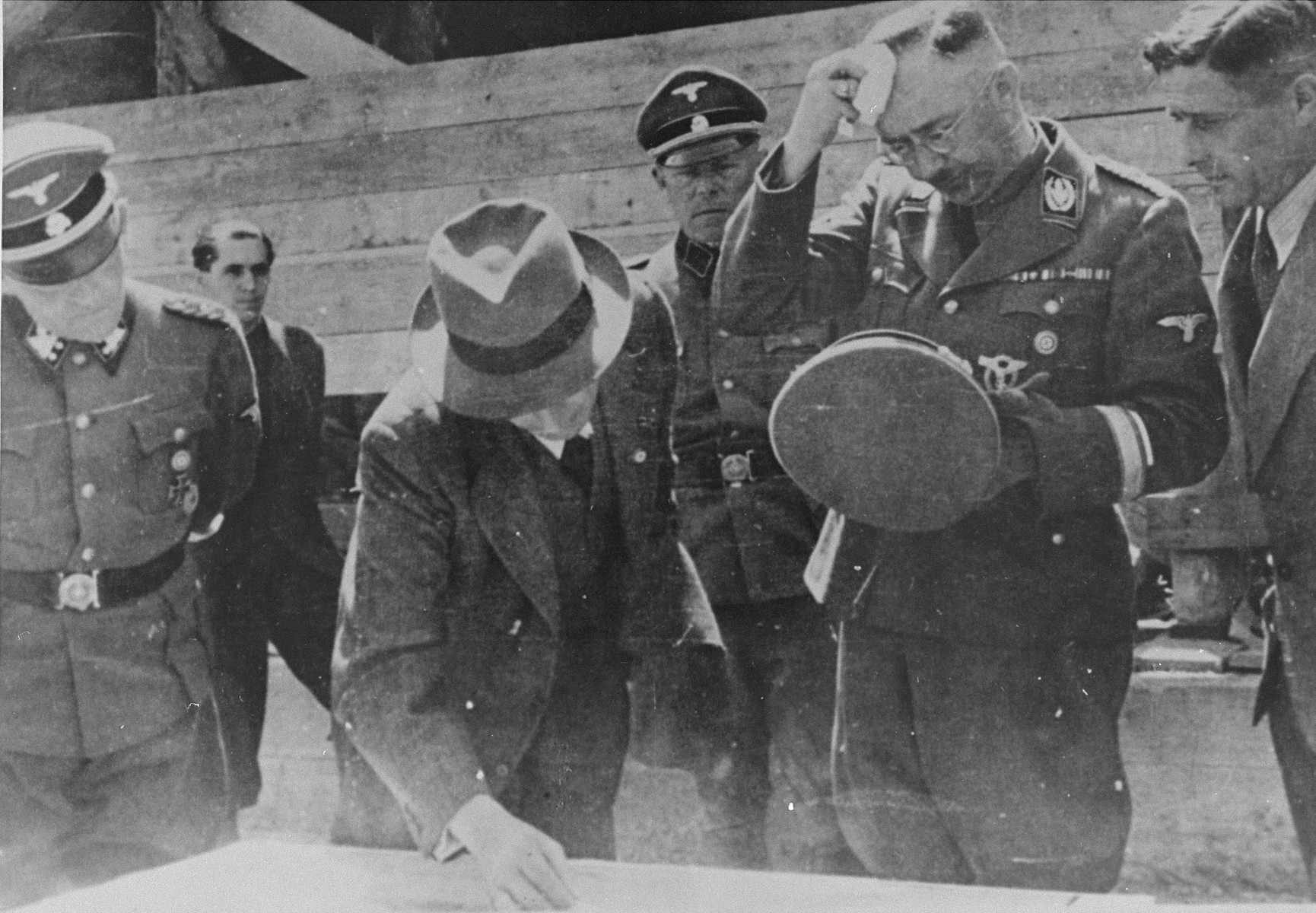 Reichsfuehrer SS Heinrich Himmler wipes his brow while examining a building plan with Max Faust (wearing the fedora) during an inspection tour of the Monowitz-Buna building site. Behind Himmler and to the right is his bodyguard Josef Kiermaier.   Faust, who was an IG Farben engineer, was the head of building operations at Monowitz-Buna.