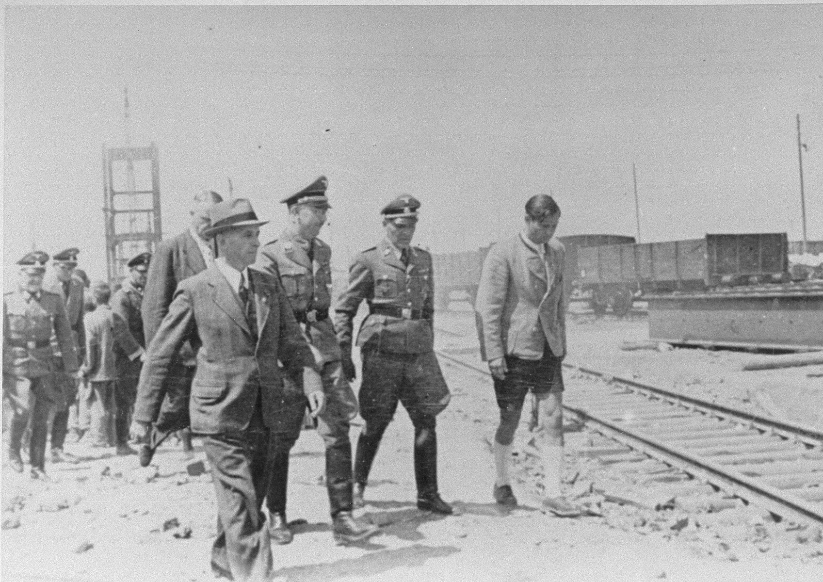 Reichsfuehrer SS Heinrich Himmler tours the Monowitz-Buna building site in the company of Max Faust (wearing the fedora) and Auschwitz commandant Rudolf Hoess (second from the right in the first row).   Faust, who was an IG Farben engineer, was the head of building operations at Monowitz-Buna.