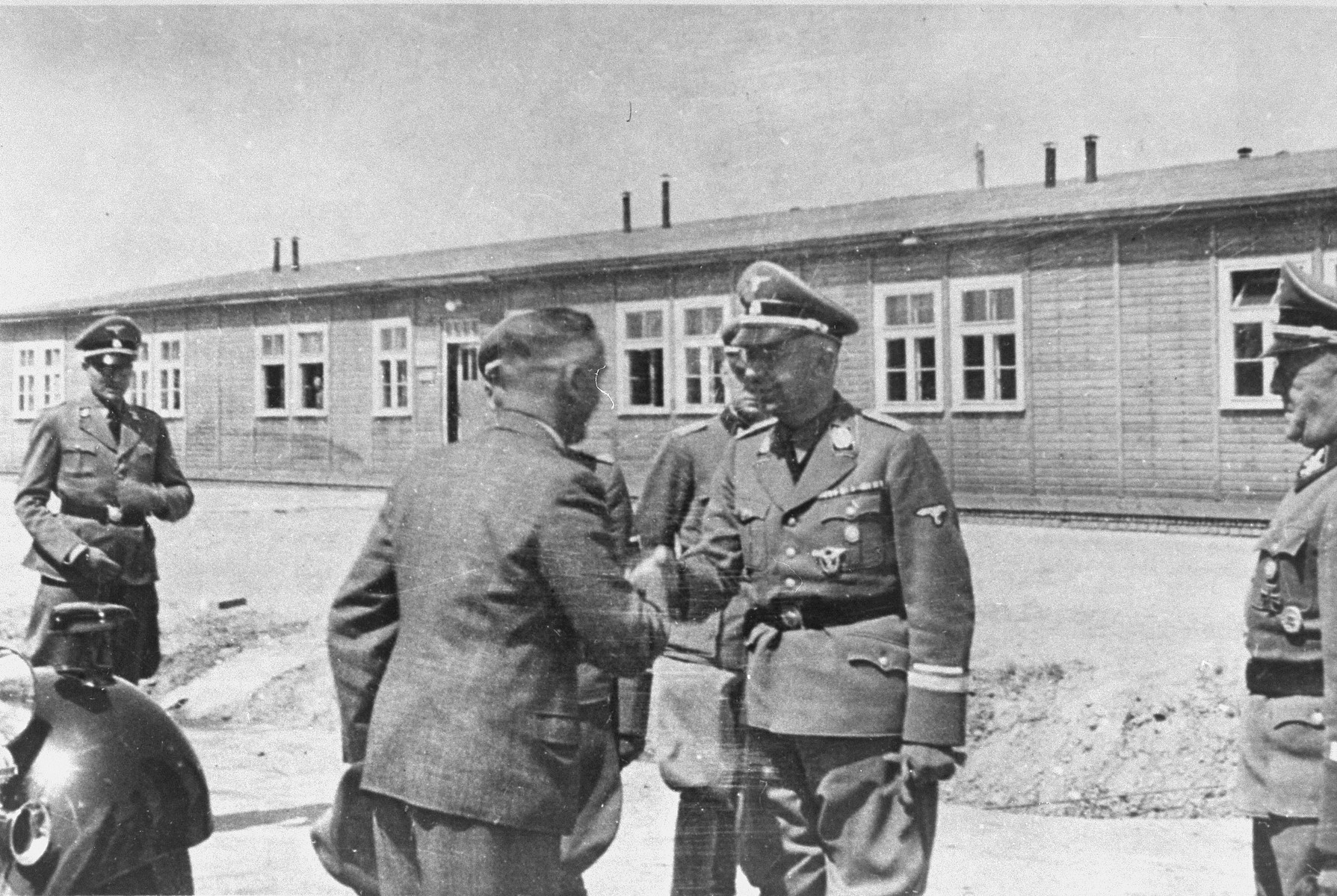 During a tour of the Monowitz-Buna building site, Reichsfuehrer SS Heinrich Himmler shakes hands with one of the engineers supervising the construction.  Gauleiter Bracht, SS-Obergruppenfuehrer Schmauser and SS-Gruppenfuehrer Kammler are accompanying Himmler.