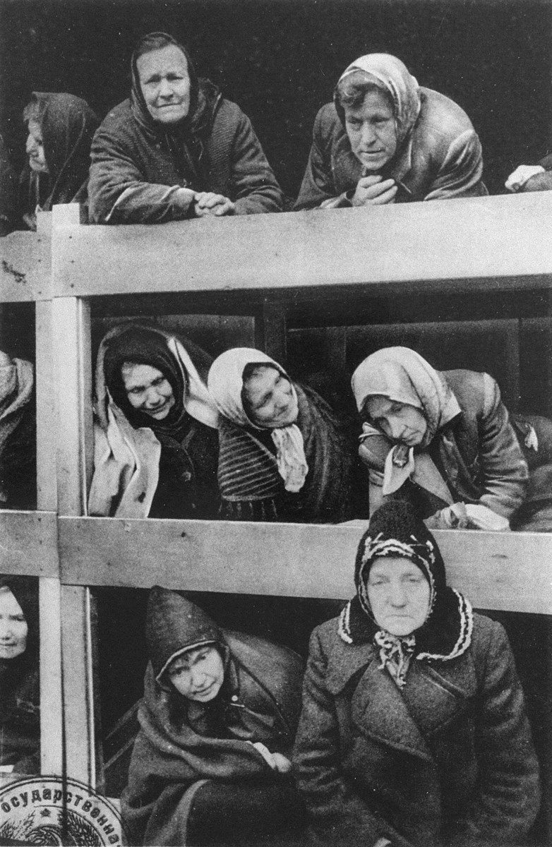 Former women prisoners on the wooden bunks that served as beds, in the Auschwitz concentration camp.  STILL PHOTOGRAPH FROM THE SOVIET FILM of the liberation of Auschwitz, taken by the film unit of the First Ukrainian Front.