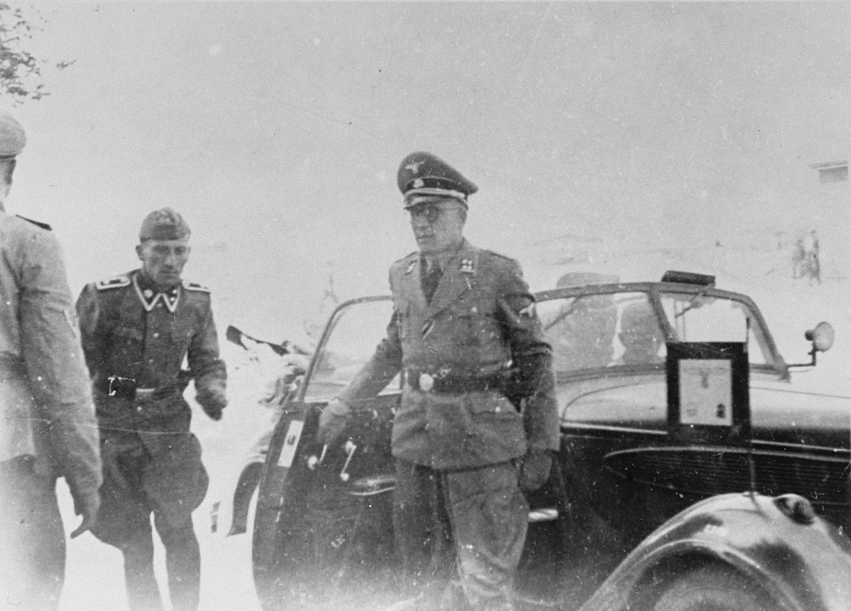 An SS officer steps out of his car during a tour of the Monowitz-Buna building site.