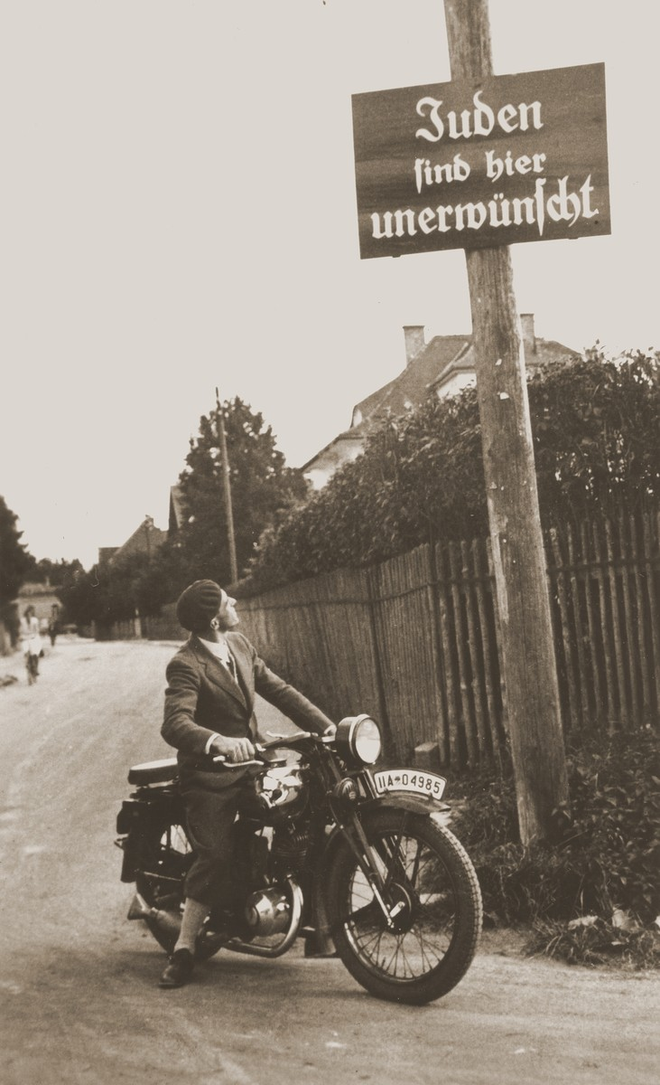 "A young man on a motorcycle gazes up at a sign posted on a telephone pole that reads, ""Jews are not welcomed here."""
